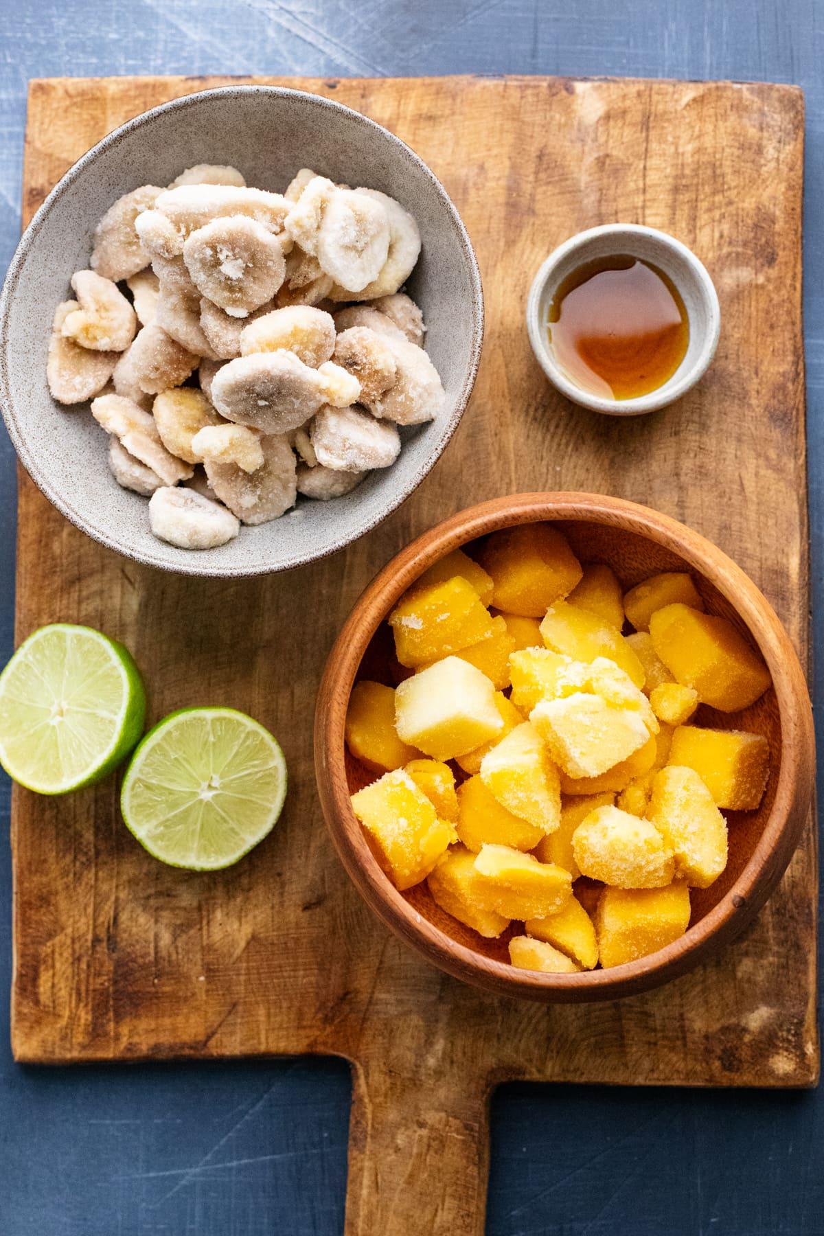 mango lime sorbet ingredients arranged on brown wooden cutting board.