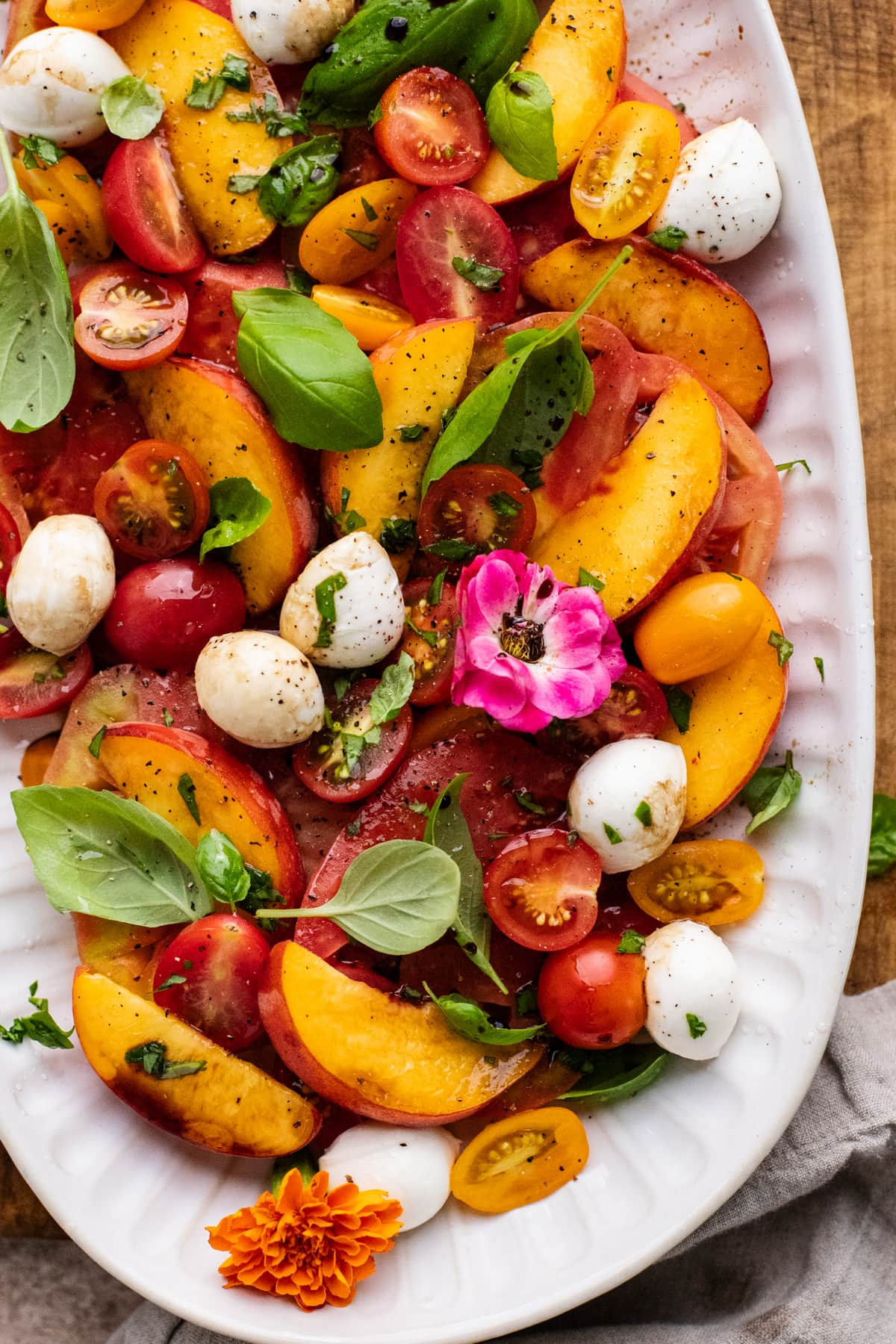 A close up of peaches in a caprese salad with basil leaves on a white plate with gray napkin next to it.
