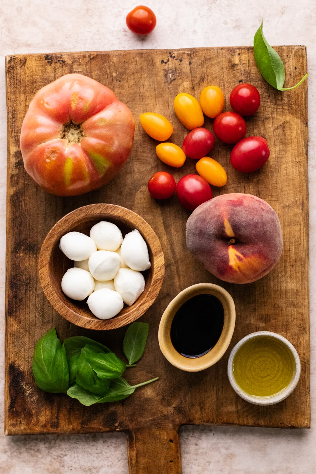 Ingredients for peach caprese salad arranged on brown wooden cutting board.