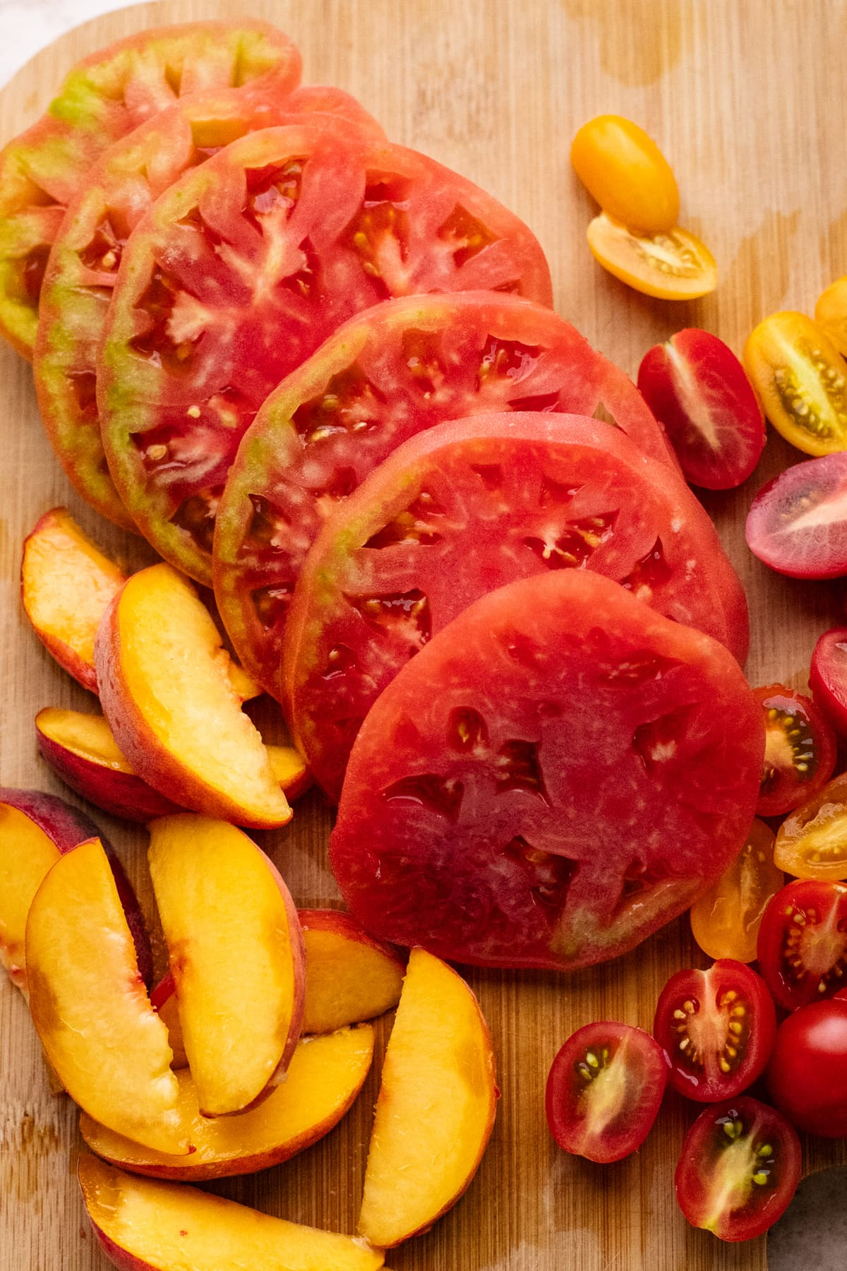 Slices of tomatoes and peaches arranged on brown wooden cutting board.