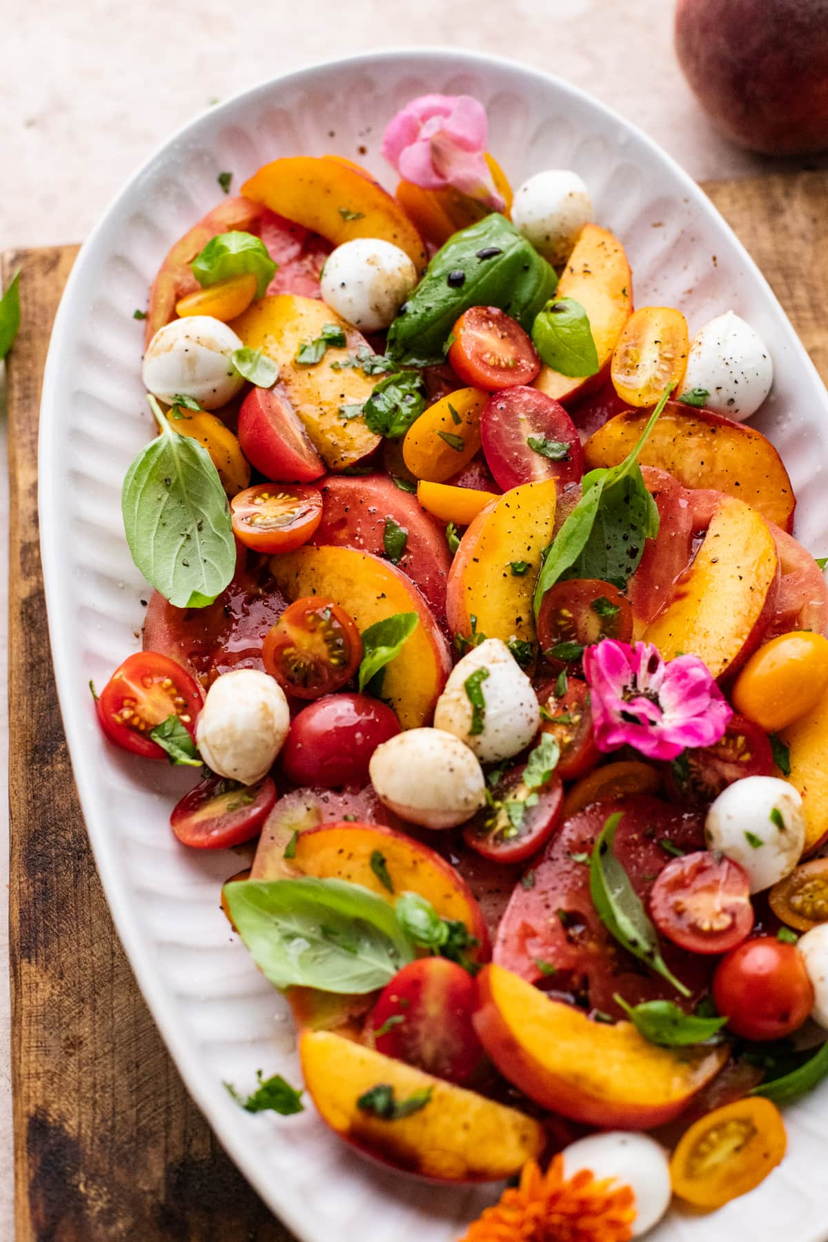 Peach caprese salad on a white plate sitting on a brown wooden cutting board.