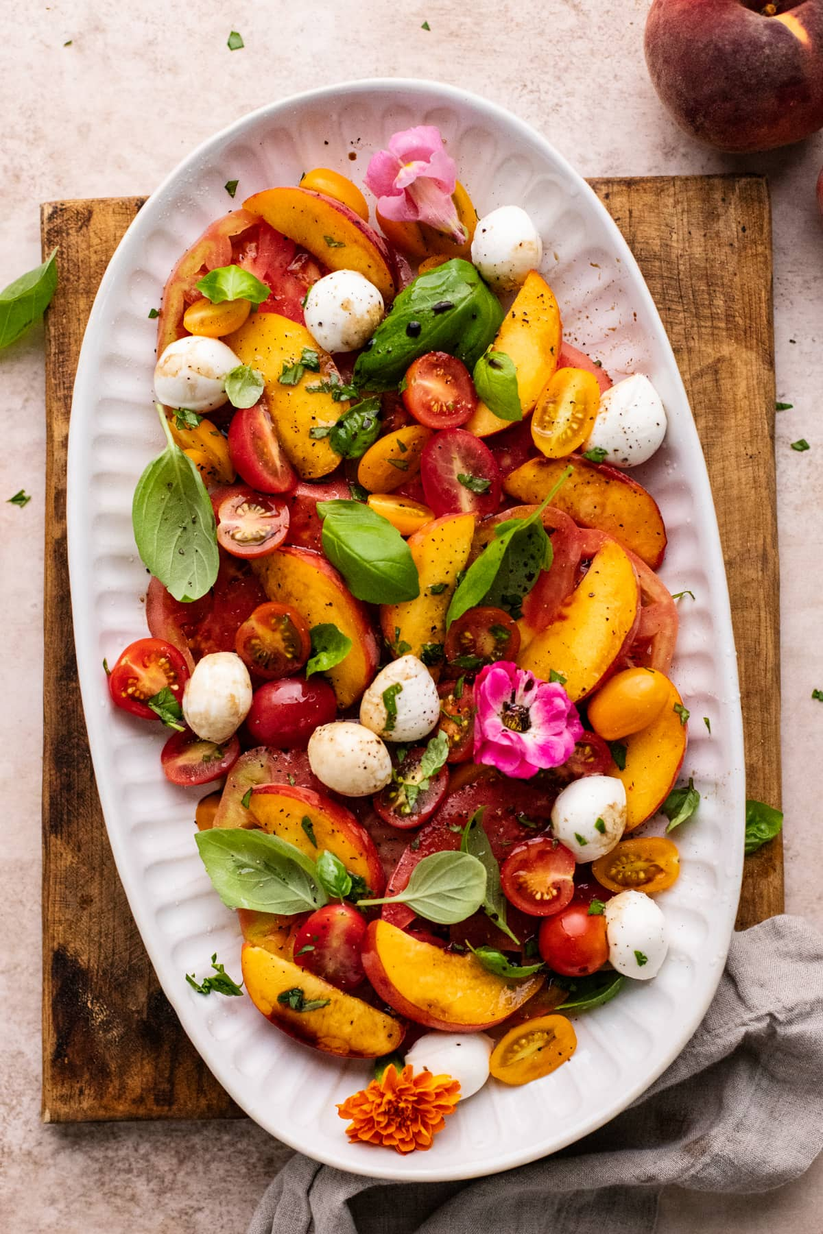 white oval plate with peach caprese salad sitting on a brown cutting board on light colored background.