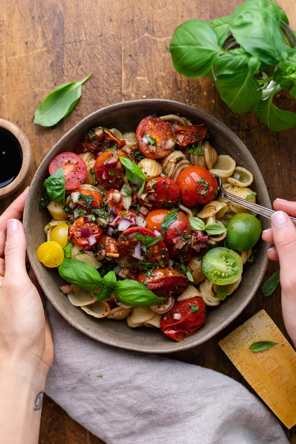 hands holding bowl with a fork in it of pasta with bruschetta in it on brown wooden board with herbs and gray napkin arranged around it.