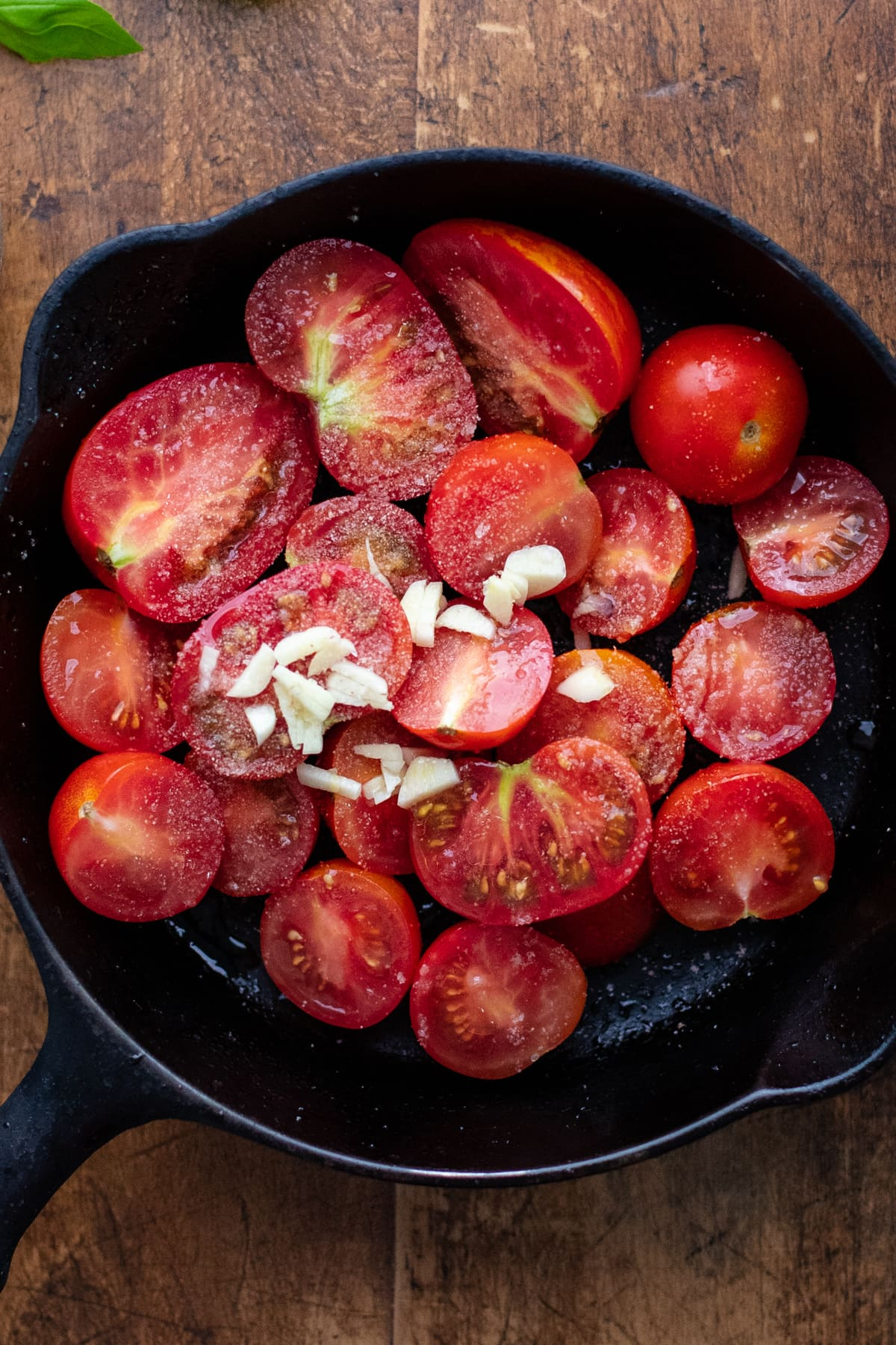 black cast iron pan with halved tomatoes in it.
