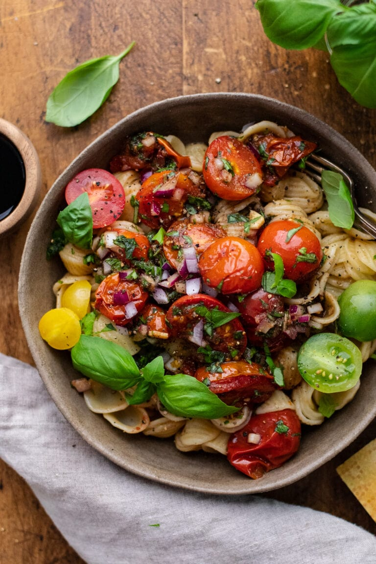 ceramic dish with bruschetta pasta with tomatoes on wooden background with gray napkin and fresh herbs arranged around it.