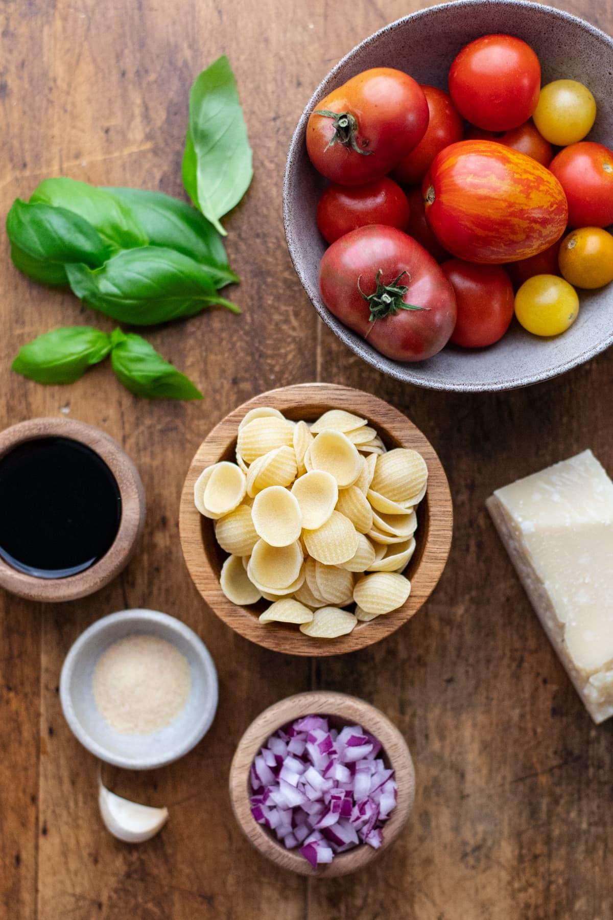 Ingredients for bruschetta pasta arranged on a wooden background.