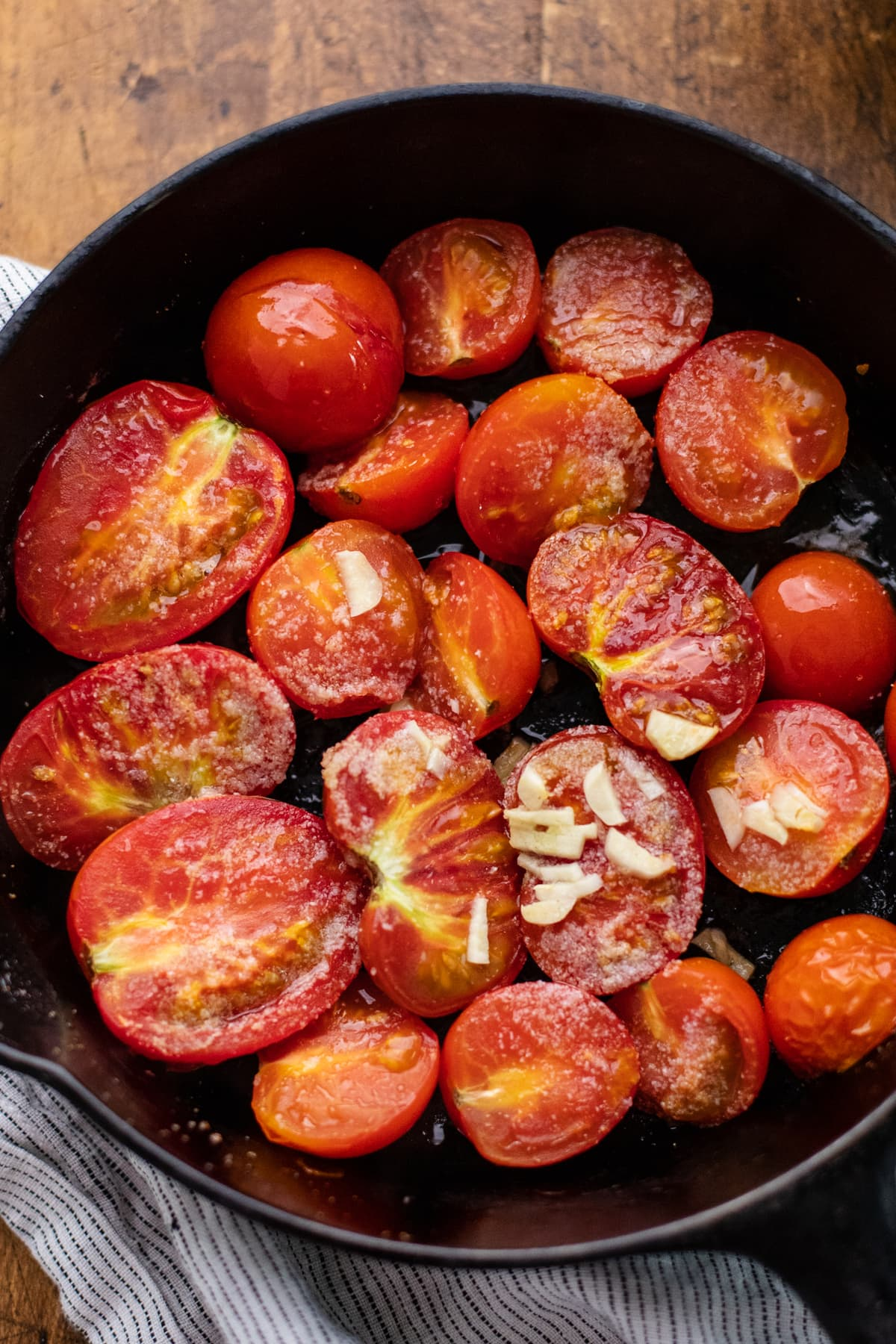 cast iron pan with roasted halved tomatoes in it on wooden background.