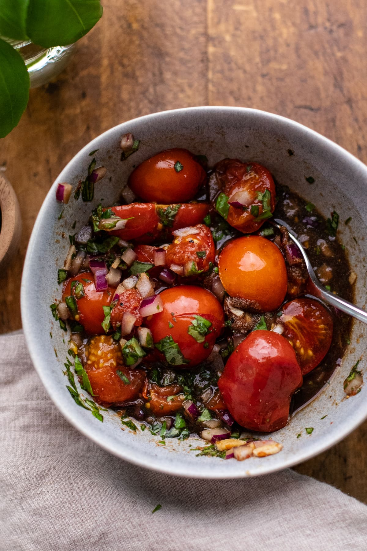 gray back with roasted tomatoes, balsamic, and herbs in it on brown wooden board.
