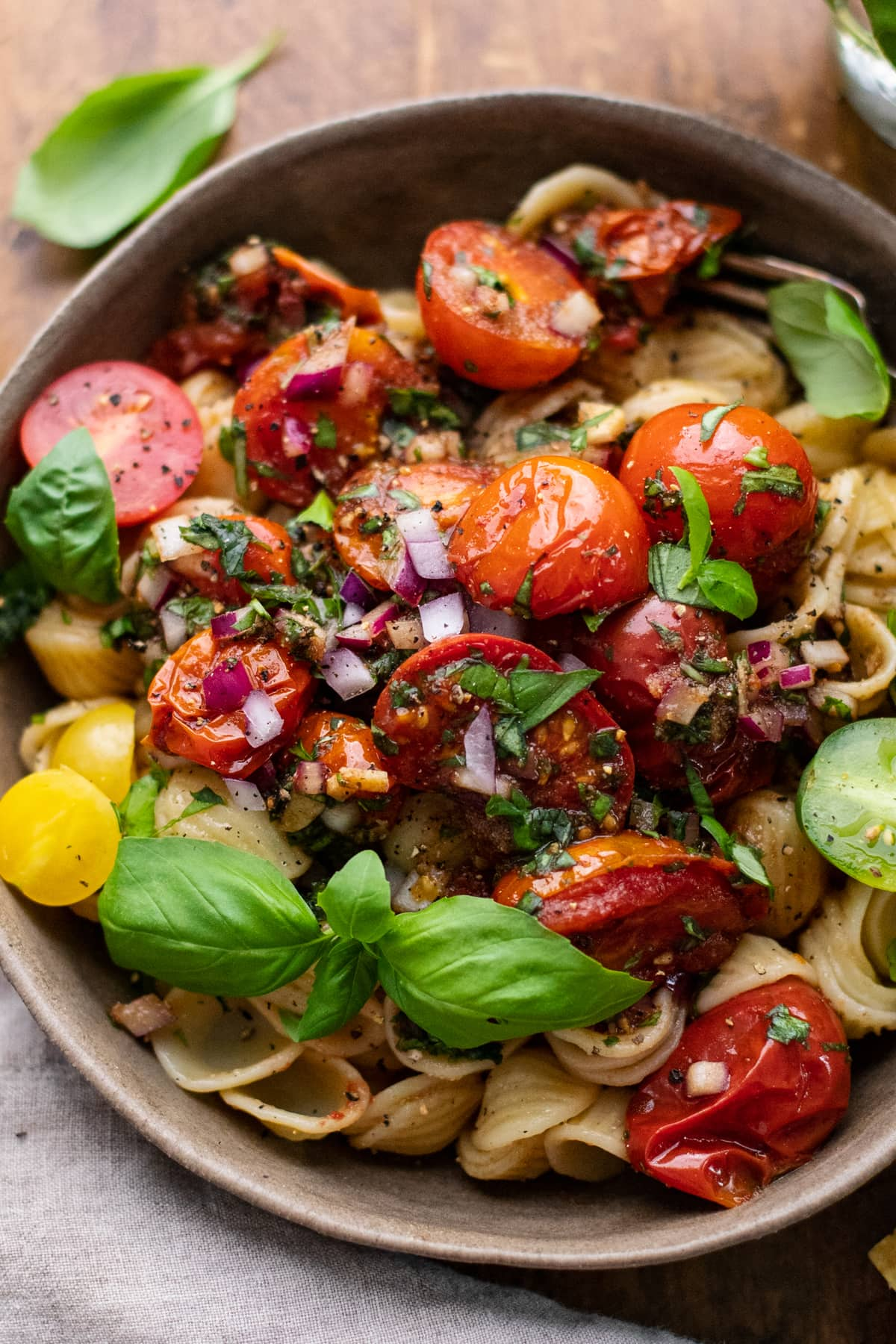 close up of bruschetta tomatoes over pasta with fresh herbs over top.