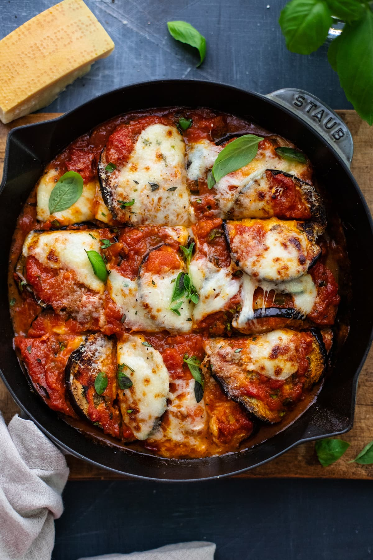 cast iron skillet with eggplant and zucchini lasagna on wooden board on a gray background.