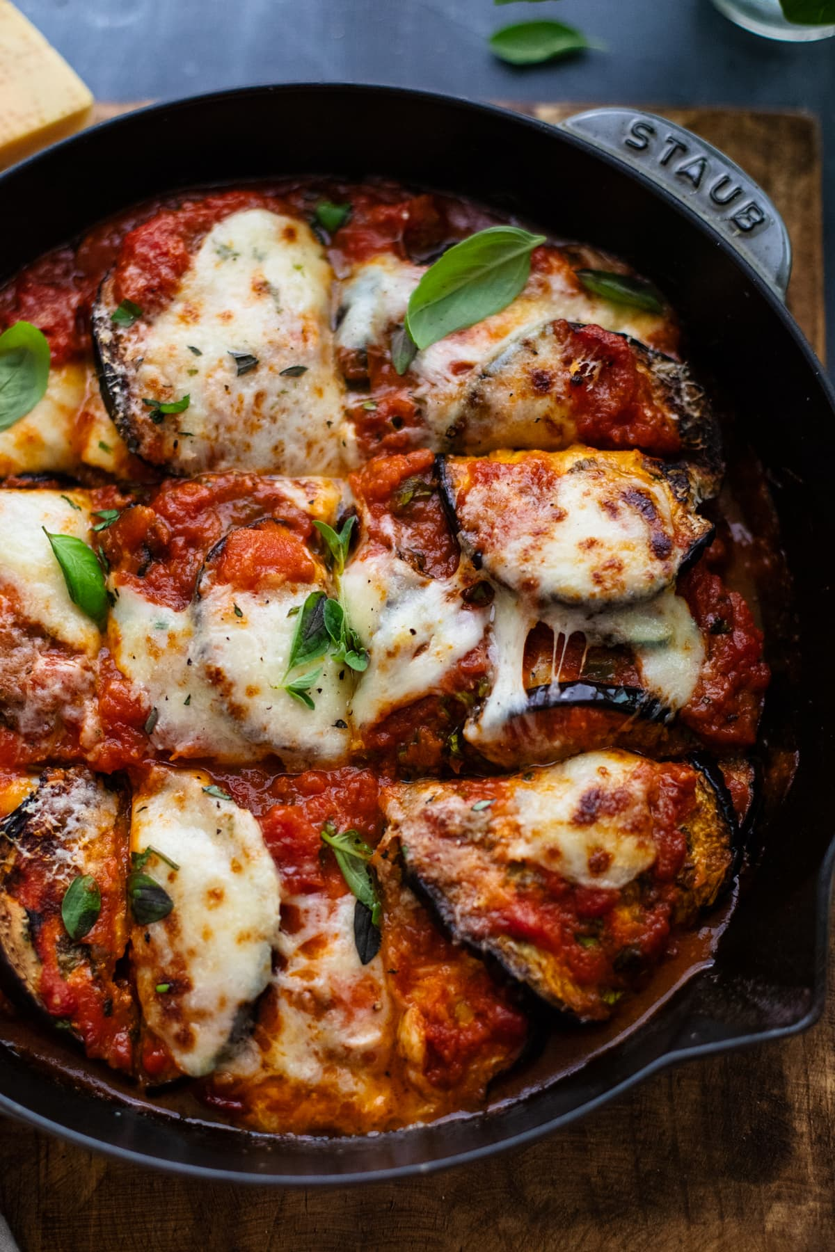 eggplant and zucchini lasagna in cast iron skillet on wooden board.