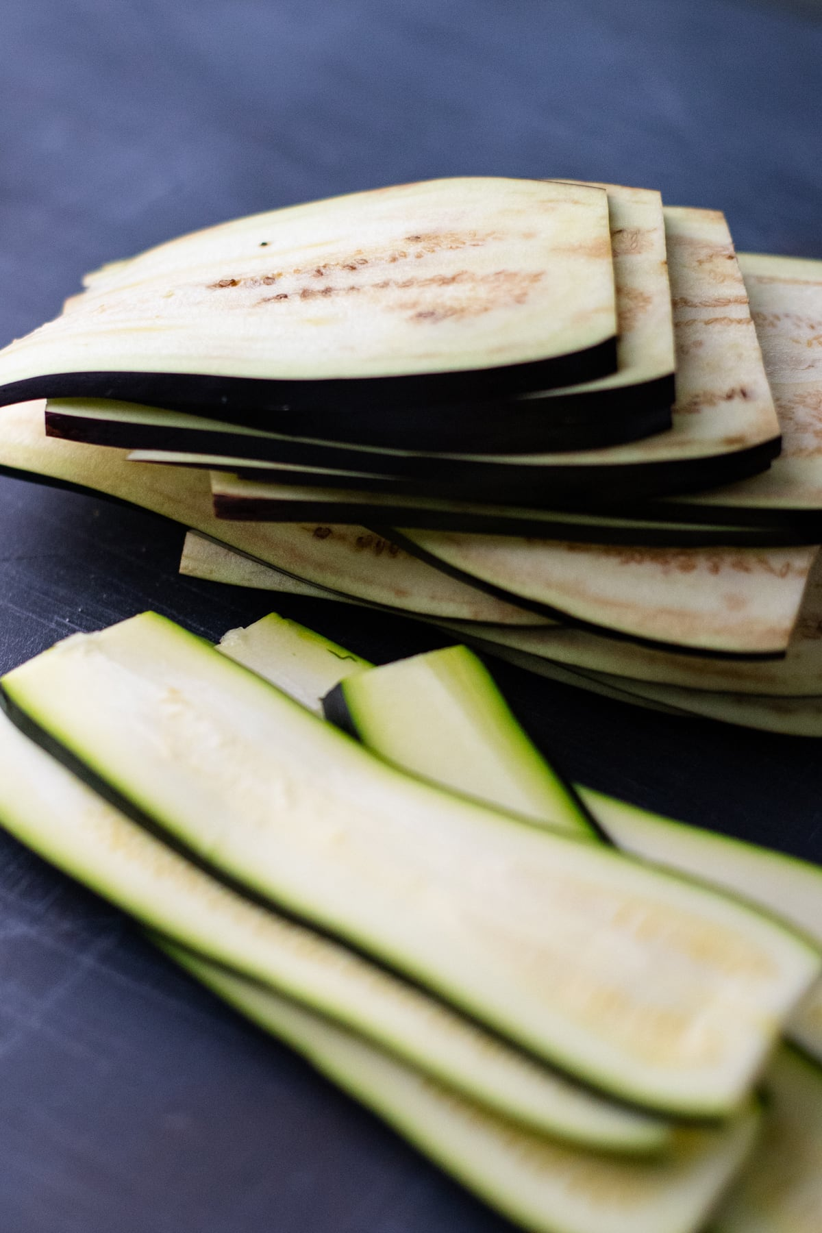 Eggplant and zucchini cut into thin slices on dark gray background.