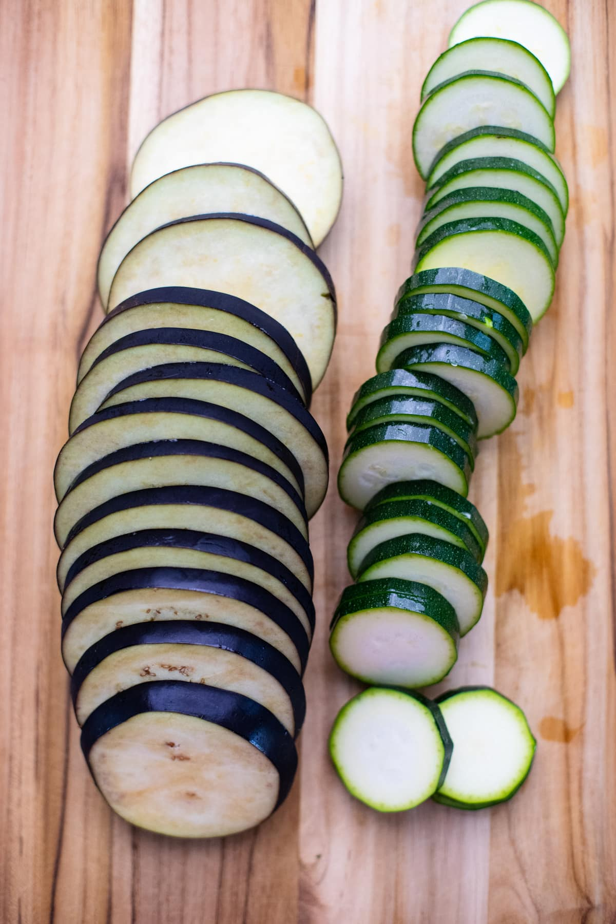 eggplant and zucchini cut into slices on wooden cutting board.