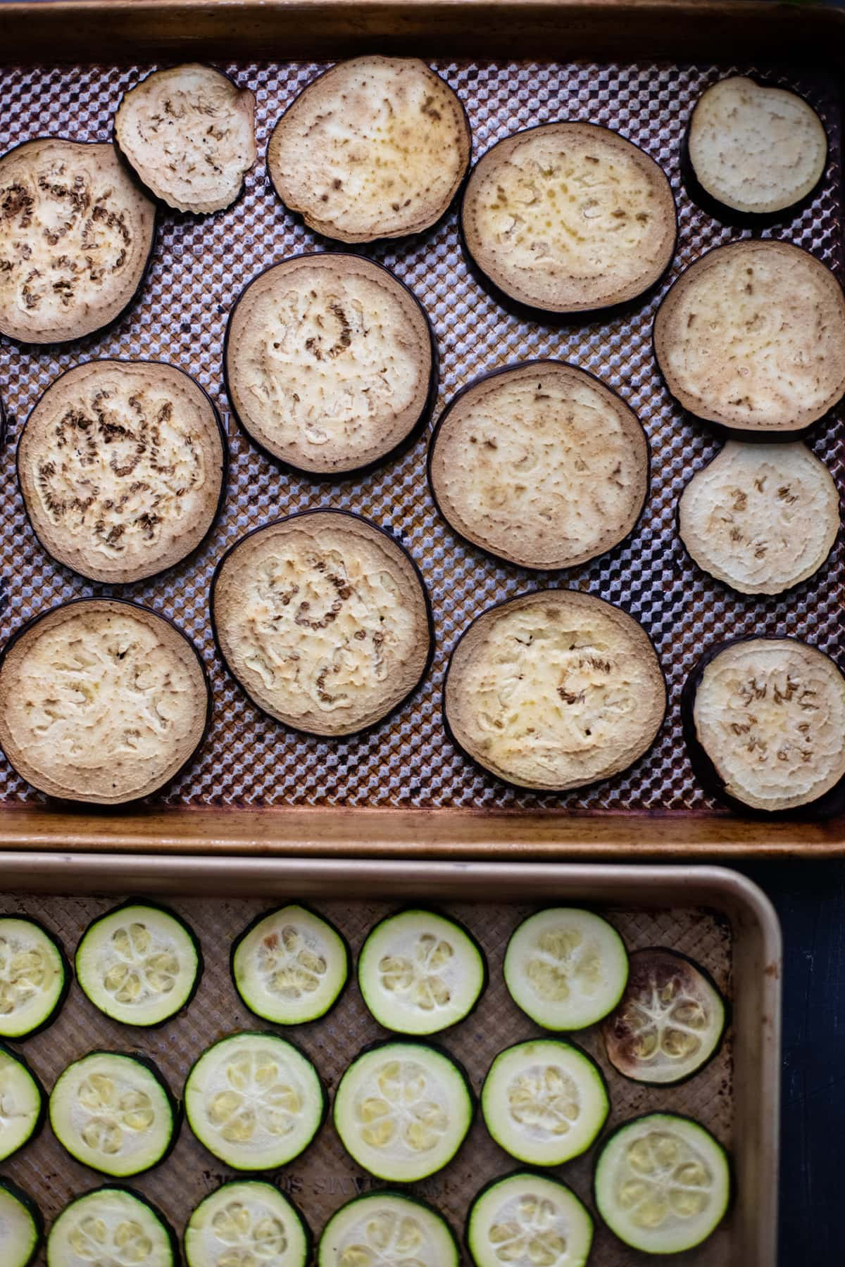 slices of roasted eggplant and zucchini arranged on sheet pans.
