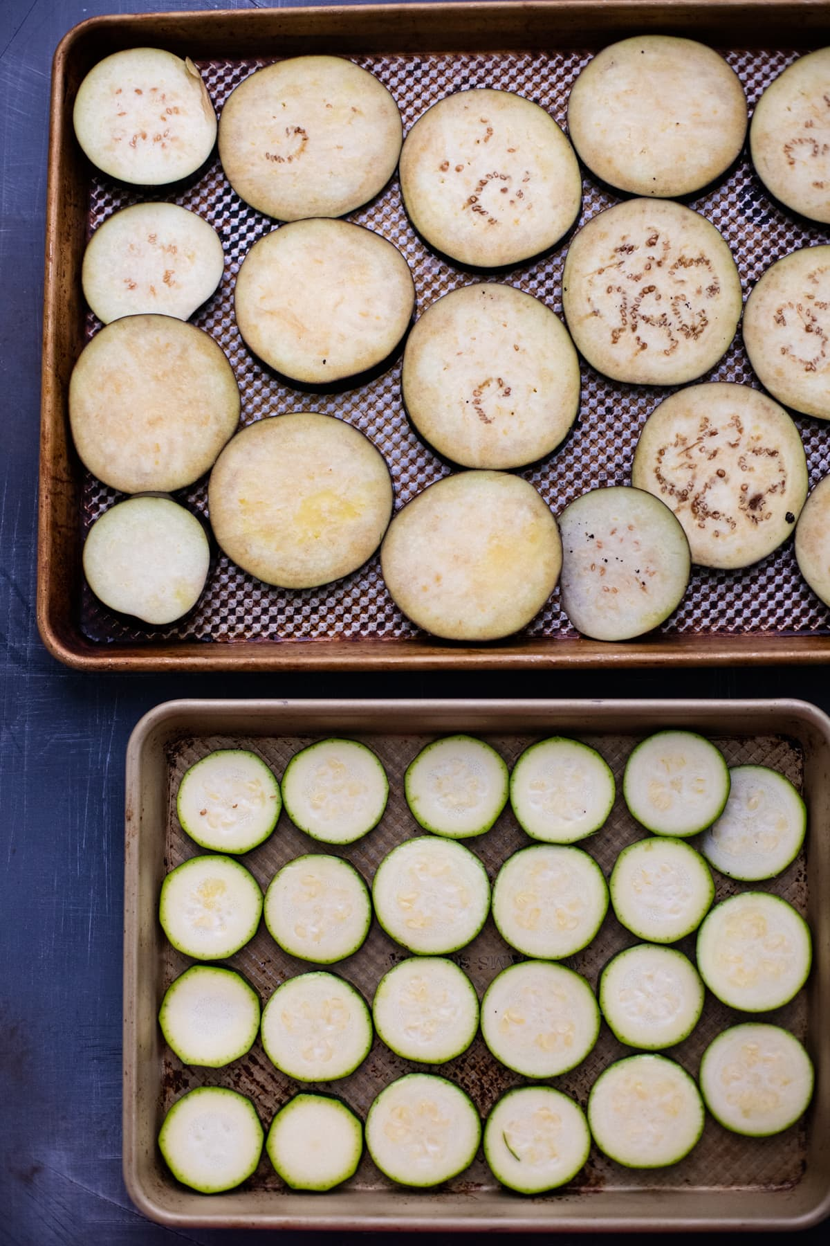 two sheet pans with slices of eggplant and zucchini on them.