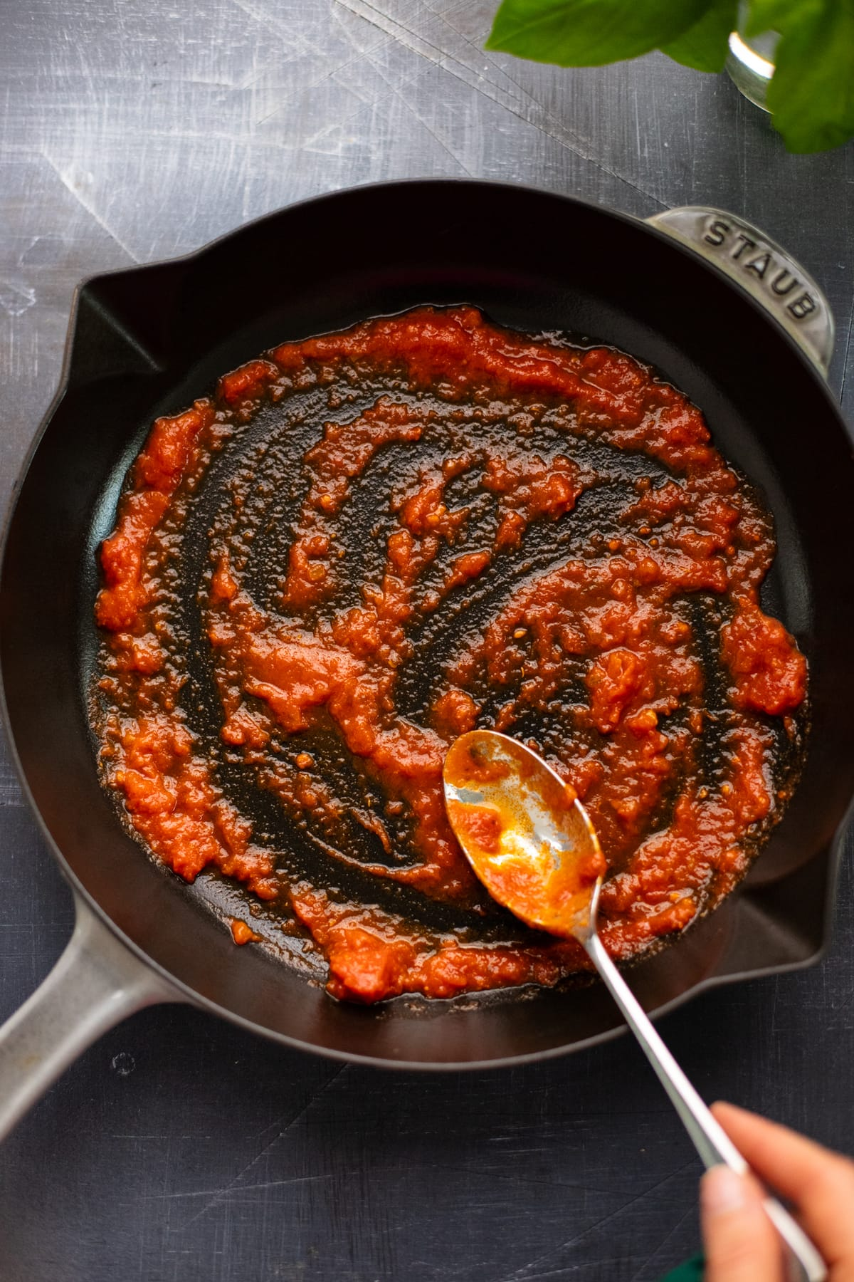 spoon spreading red tomato sauce in cast iron pan on dark gray background.