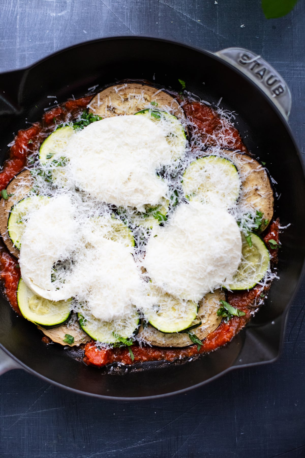 eggplant and zucchini lasagna topped with cheese in cast iron skillet.