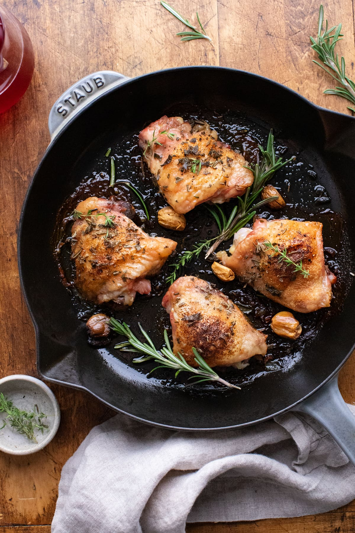 Cast iron skillet with roasted chicken thighs and herbs in it, sitting on a brown wooden background.
