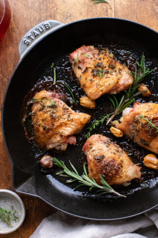 Cast iron skillet with roasted chicken thighs and herbs in it, sitting on a wooden background.