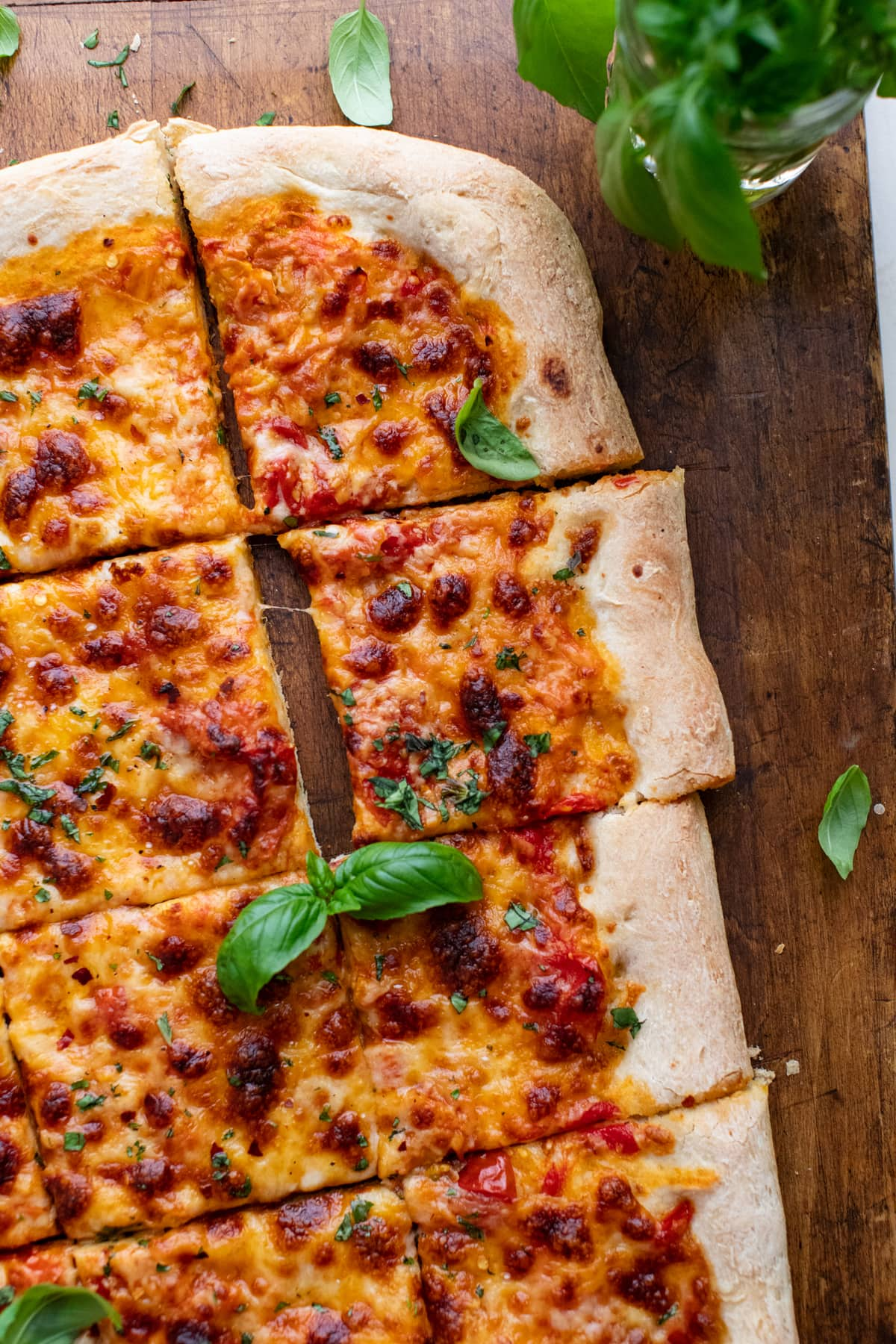 rectangle-shaped pizza cut into slices on a wooden board with fresh herbs arranged around it.