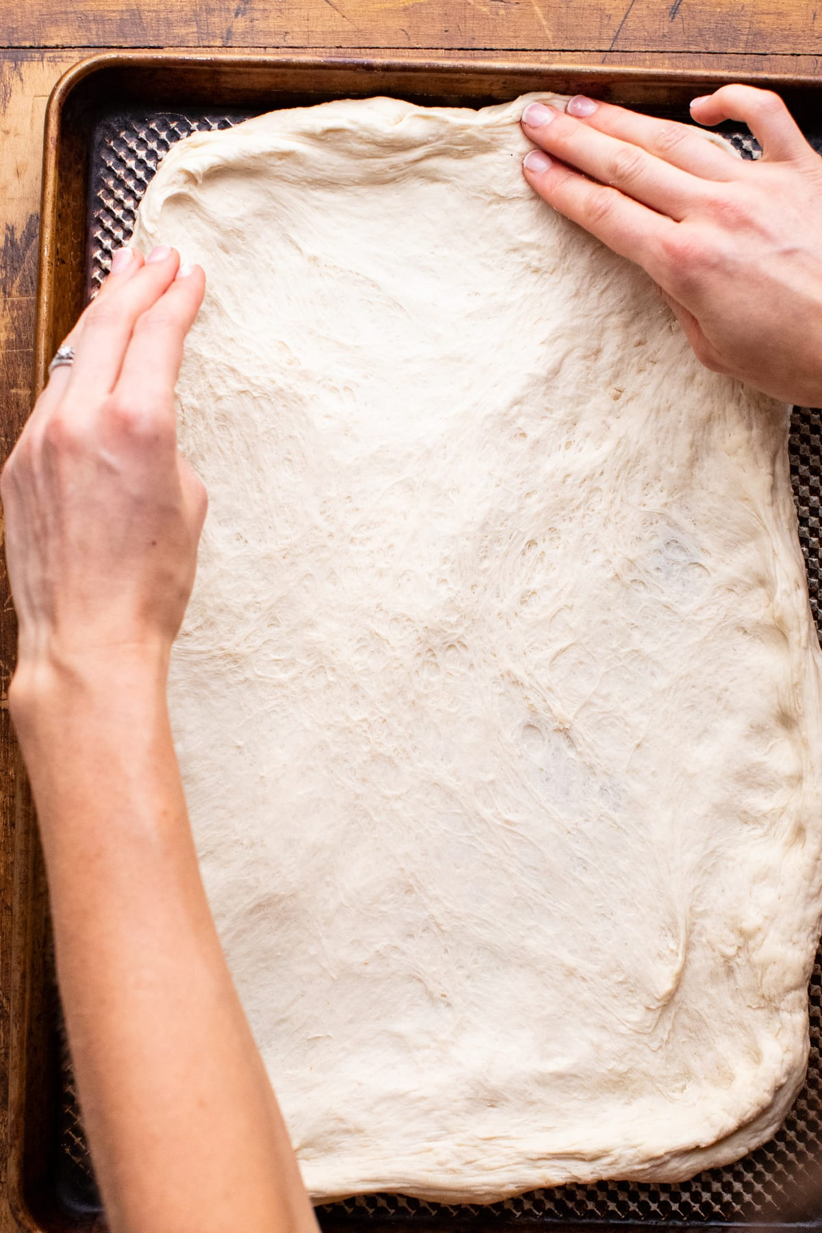 two hands forming pizza dough on a large sheet pan.