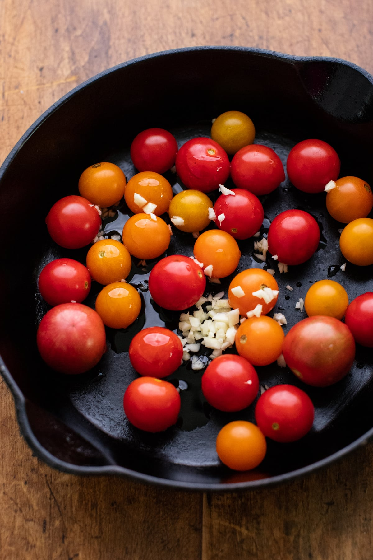 A black cast iron skillet with orange and red cherry tomatoes and minced garlic in it.