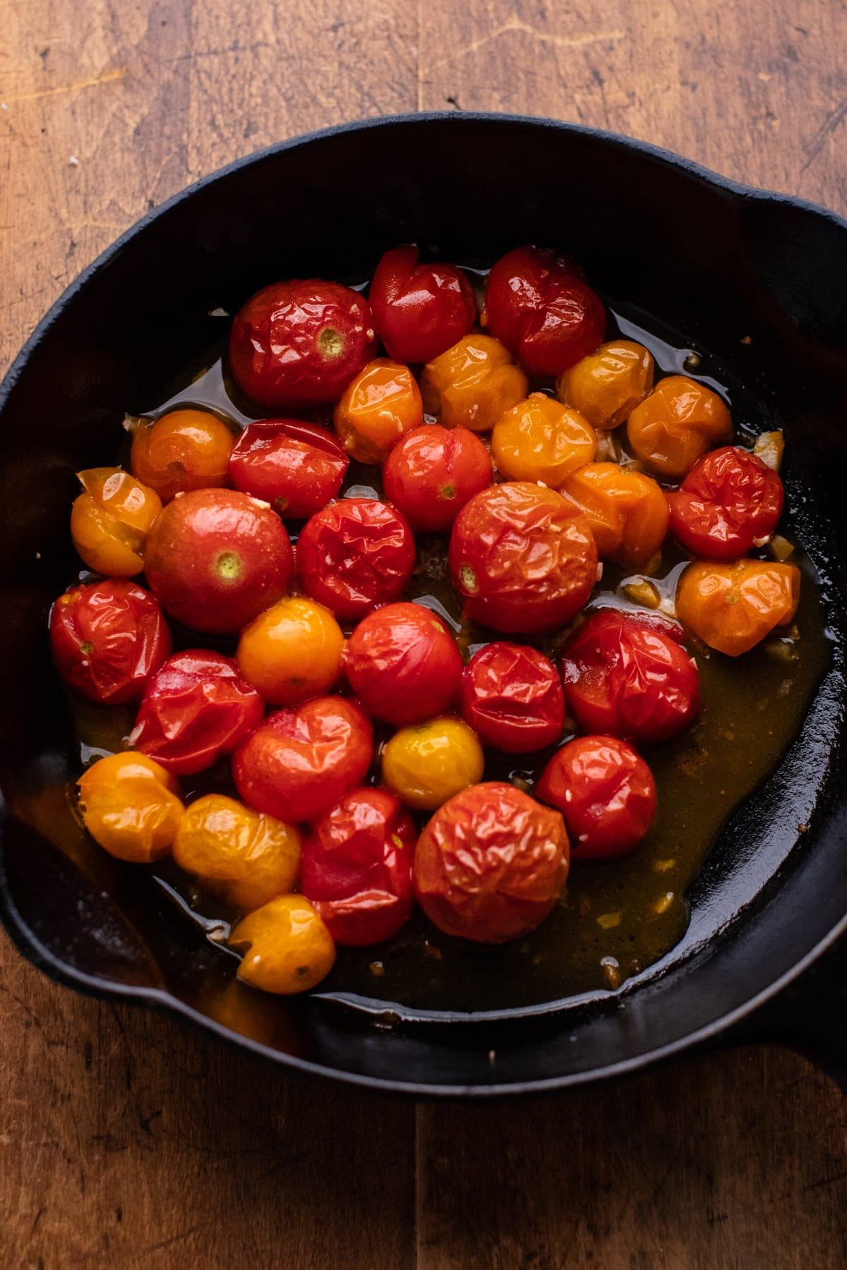 roasted cherry tomatoes in a black cast iron skillet on a wooden background.