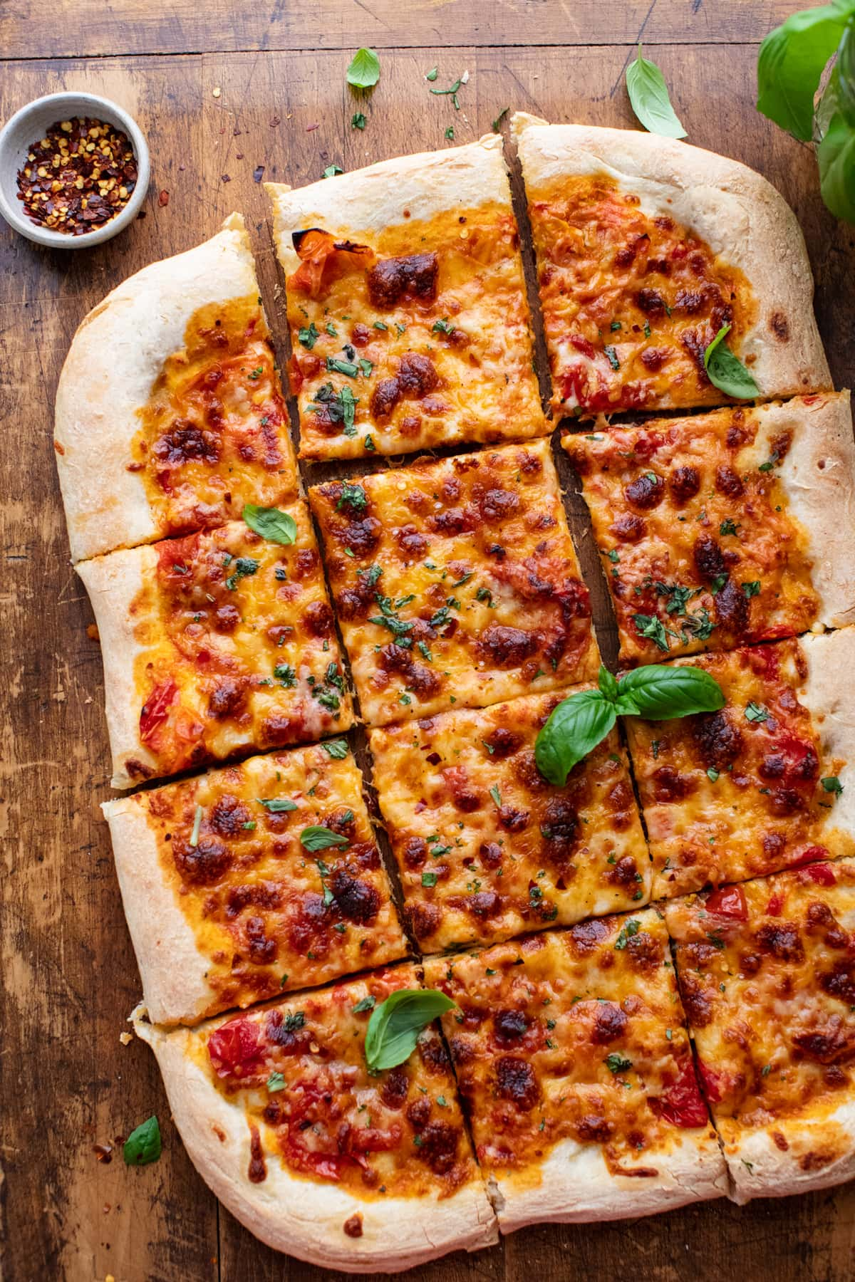 rectangle-shaped sheet pan pizza sliced into pieces on a wooden cutting board with herbs arranged around it.