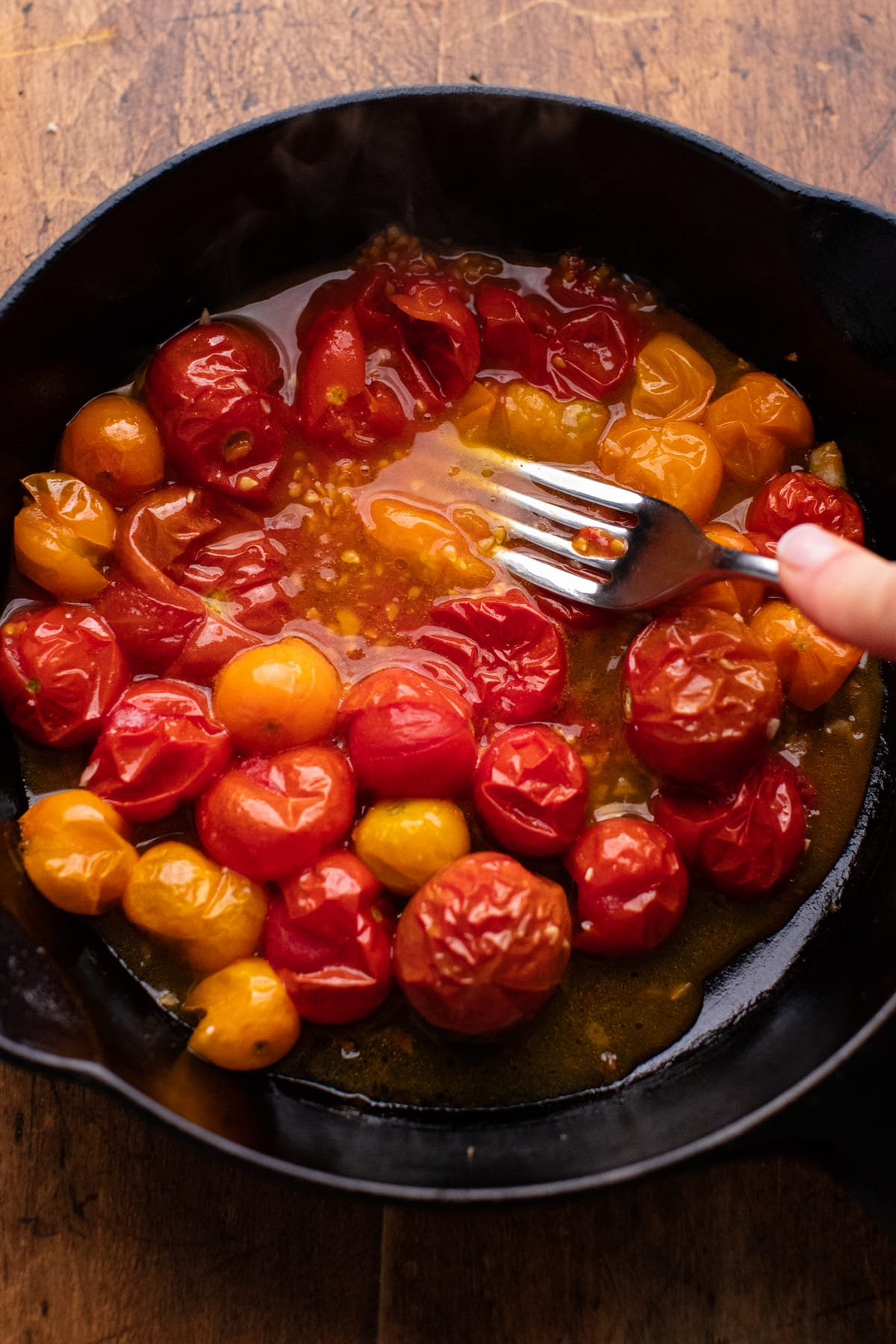 A fork mashing roasted tomatoes in a black cast iron skillet.