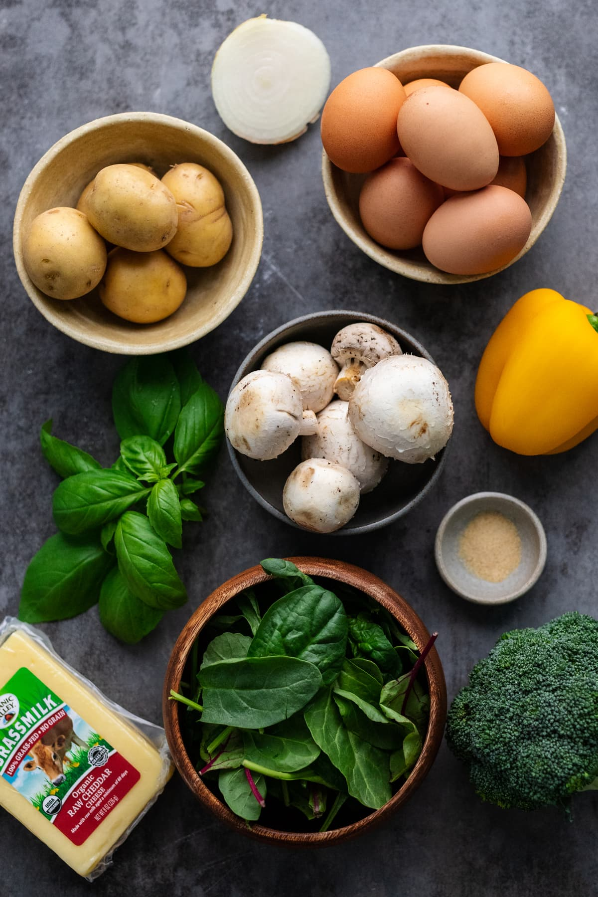 Ingredients for a breakfast egg casserole arranged on a gray background.