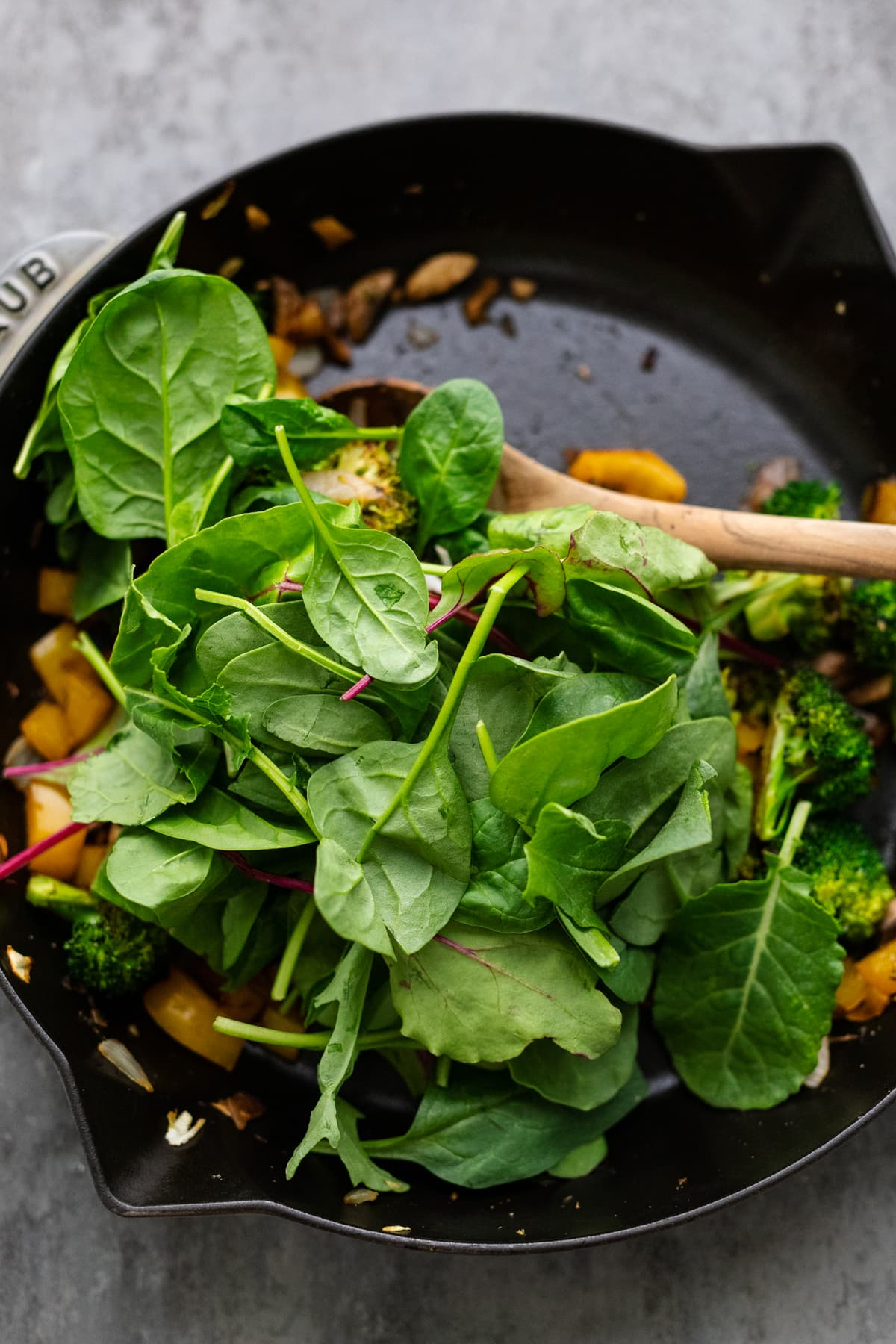 Spinach being folded into sautéed vegetables in a black cast iron skillet.