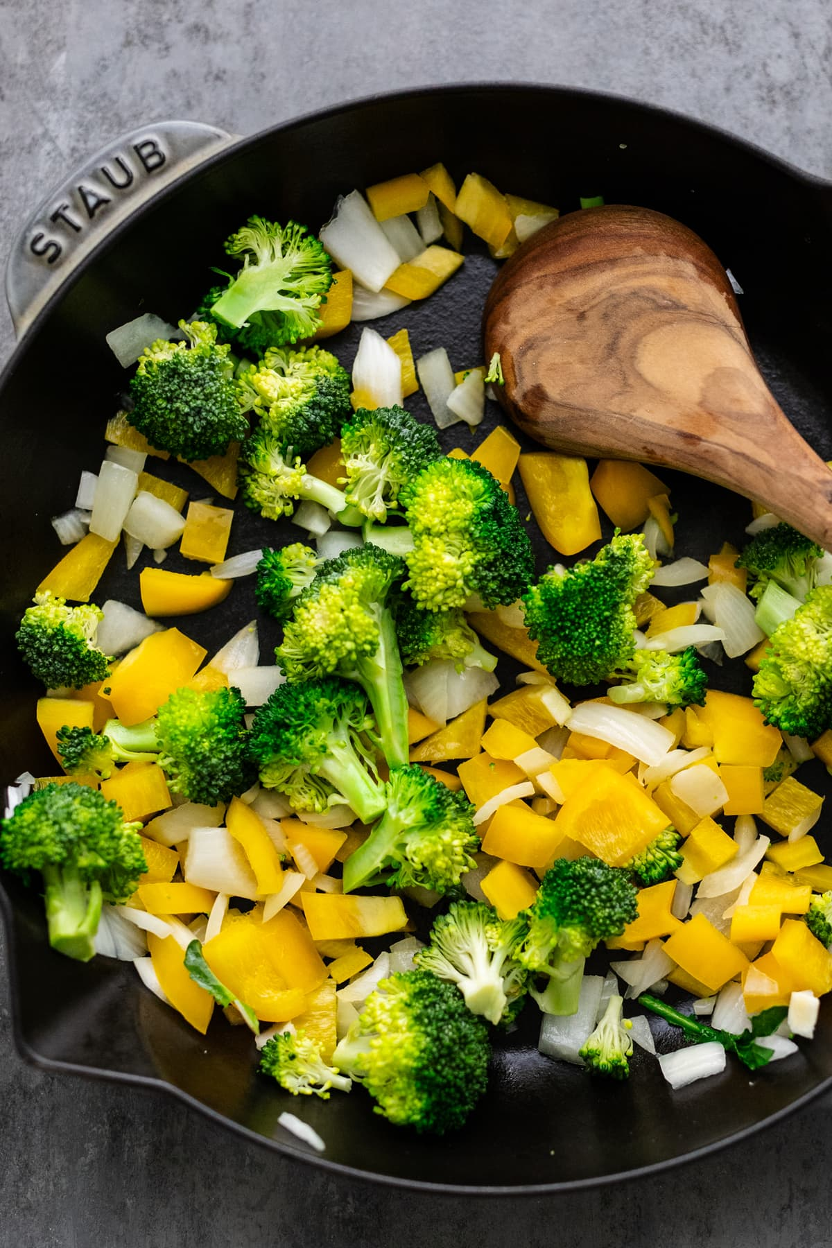 Wooden spoon sautéing chopped vegetables in a black cast iron skillet.
