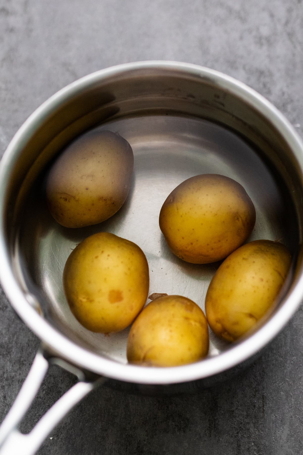A stainless steel pot with yellow potatoes and water in it.