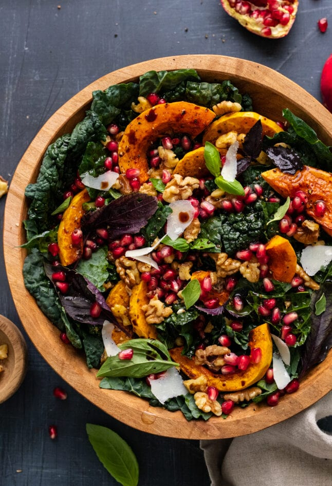 Butternut squash salad with kale and pomegranate seeds in a wooden bowl that's arranged on a dark gray background.