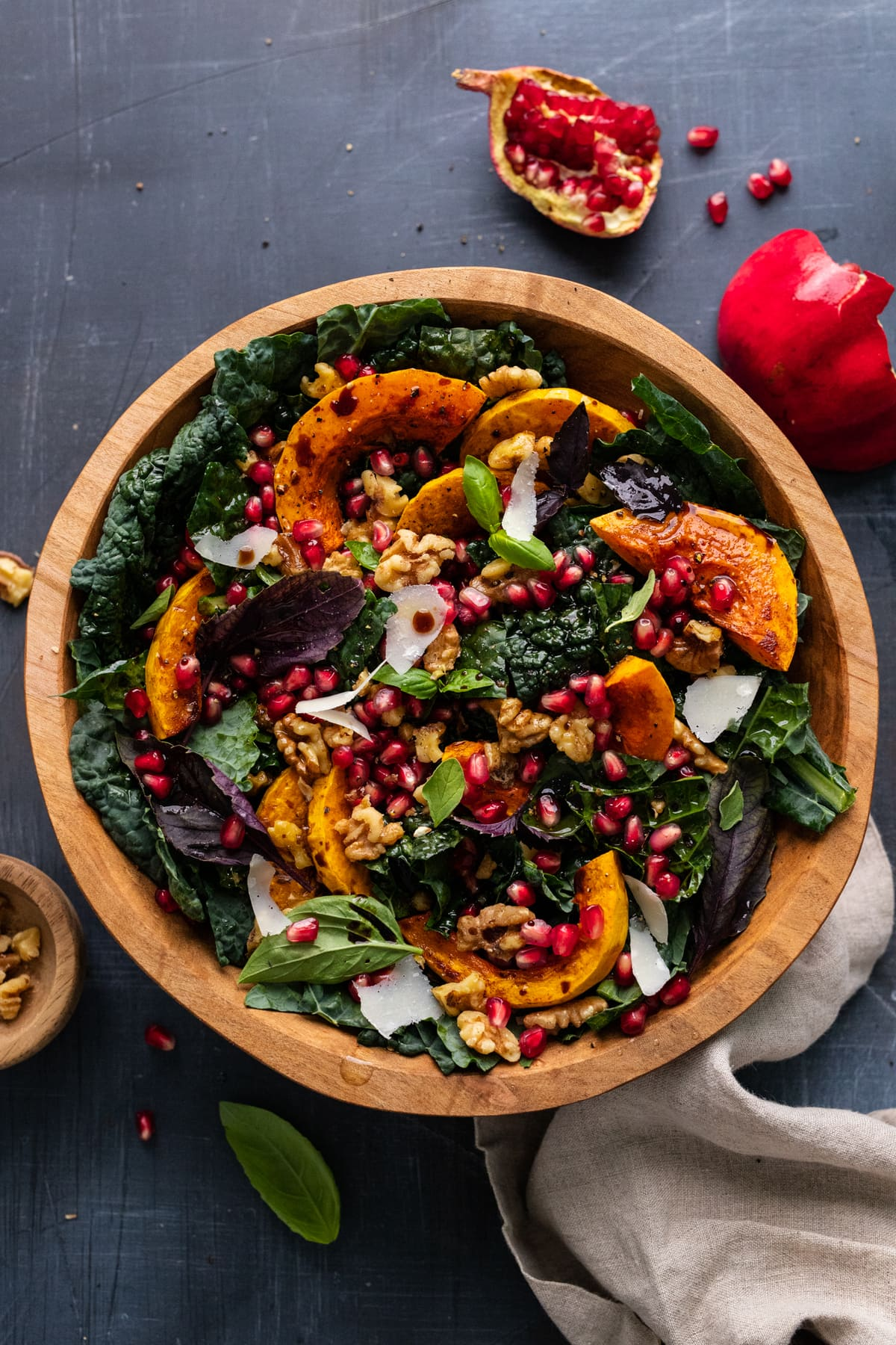 Butternut squash salad with kale and pomegranate seeds in a large wooden bowl. The salad is displayed on a gray background with a gray napkin, pomegranate seeds, and nuts arranged next to it.