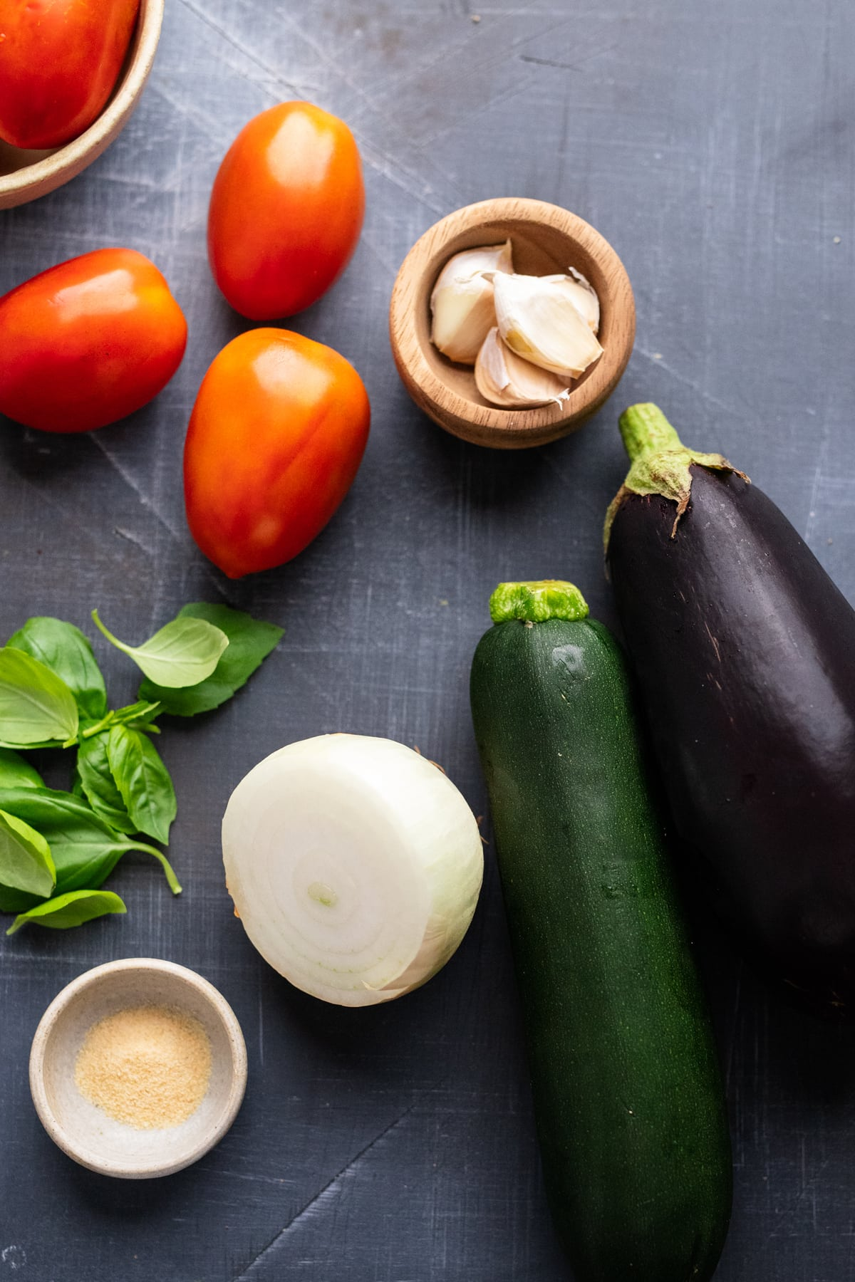 Ingredients for eggplant ratatouille arranged on a gray background.