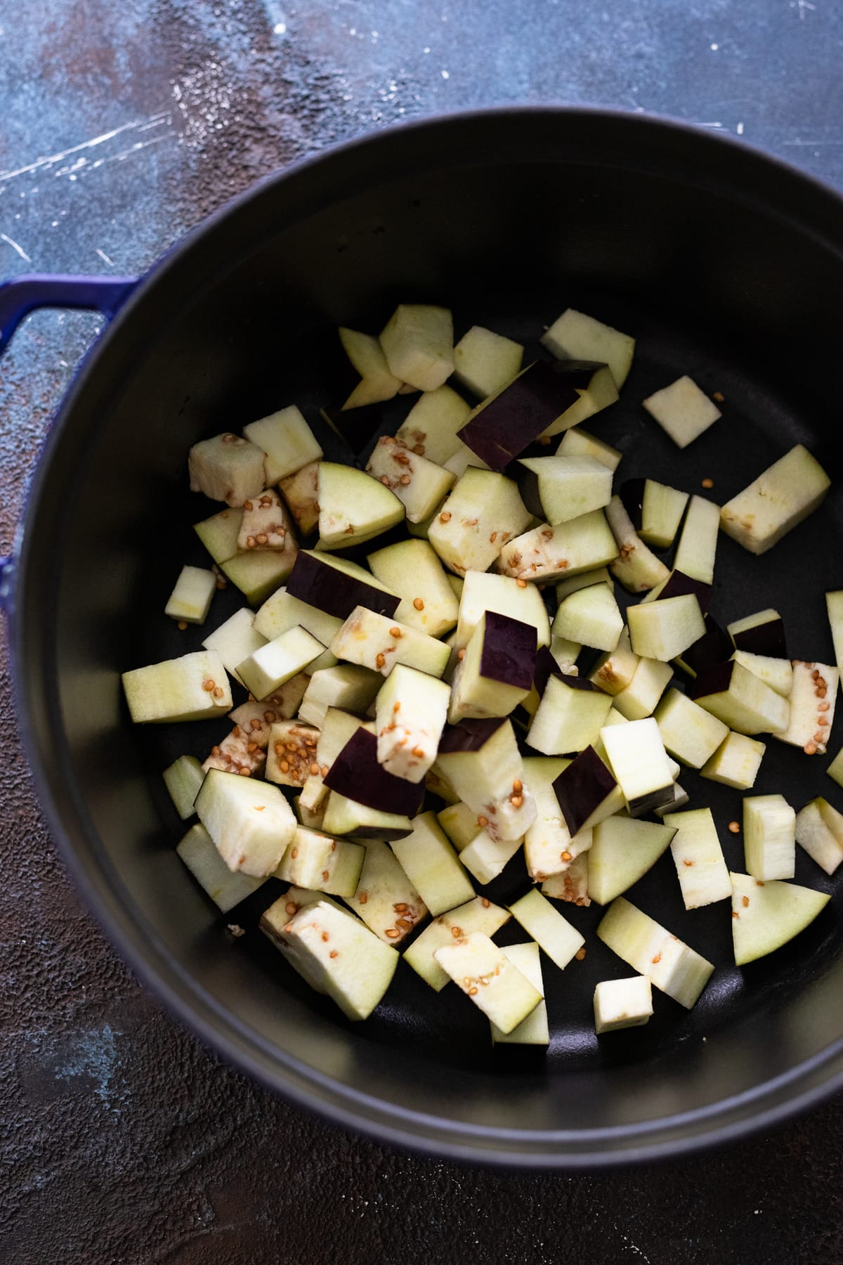 A cast iron dutch oven with cubed eggplant it it.