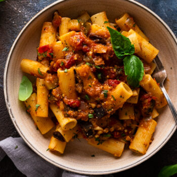 A bowl of eggplant ratatouille and pasta noodles sitting on a dark background. Around the bowl of pasta is a light gray napkin, fresh herbs, and a glass of water.