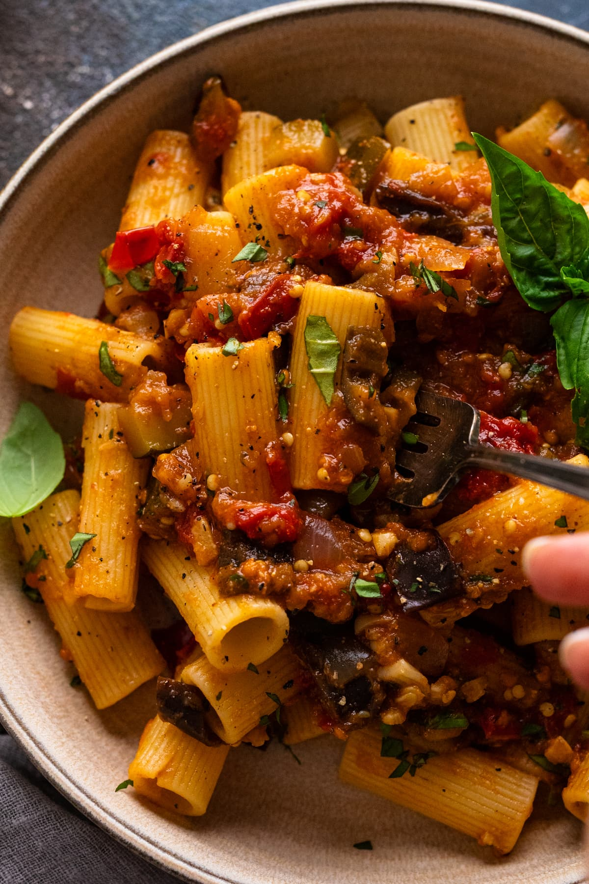 A close up of a fork in a bowl of eggplant ratatouille and pasta.