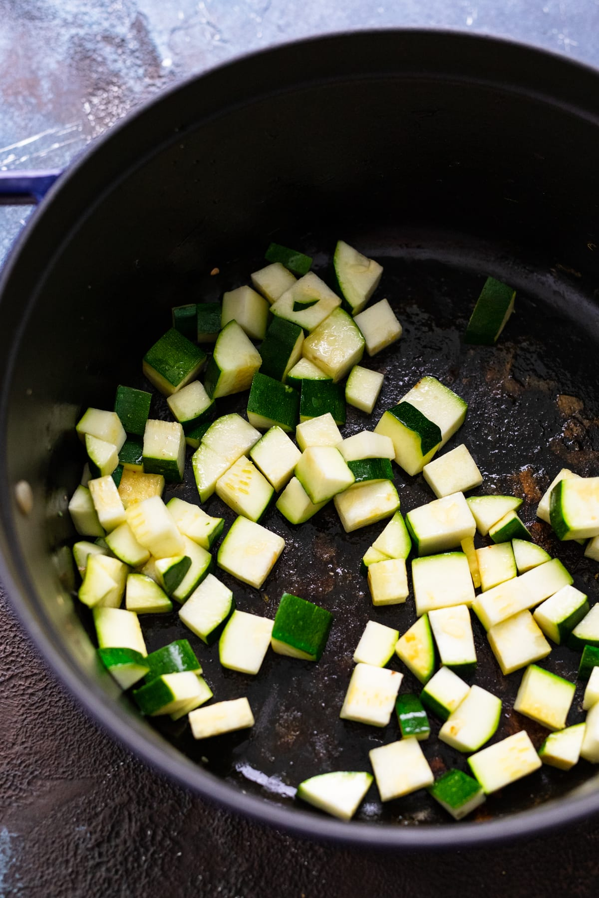 A black cast iron pot with cubed zucchini being sautéed in it.