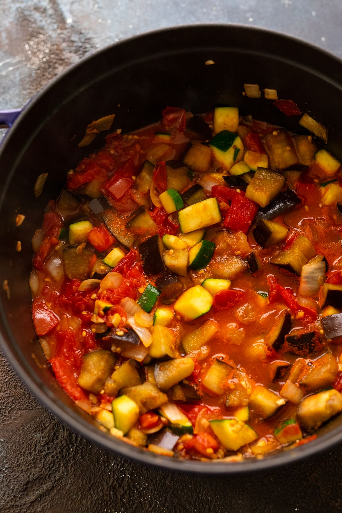 Ratatouille being simmered in a large black cast iron dutch oven pot.