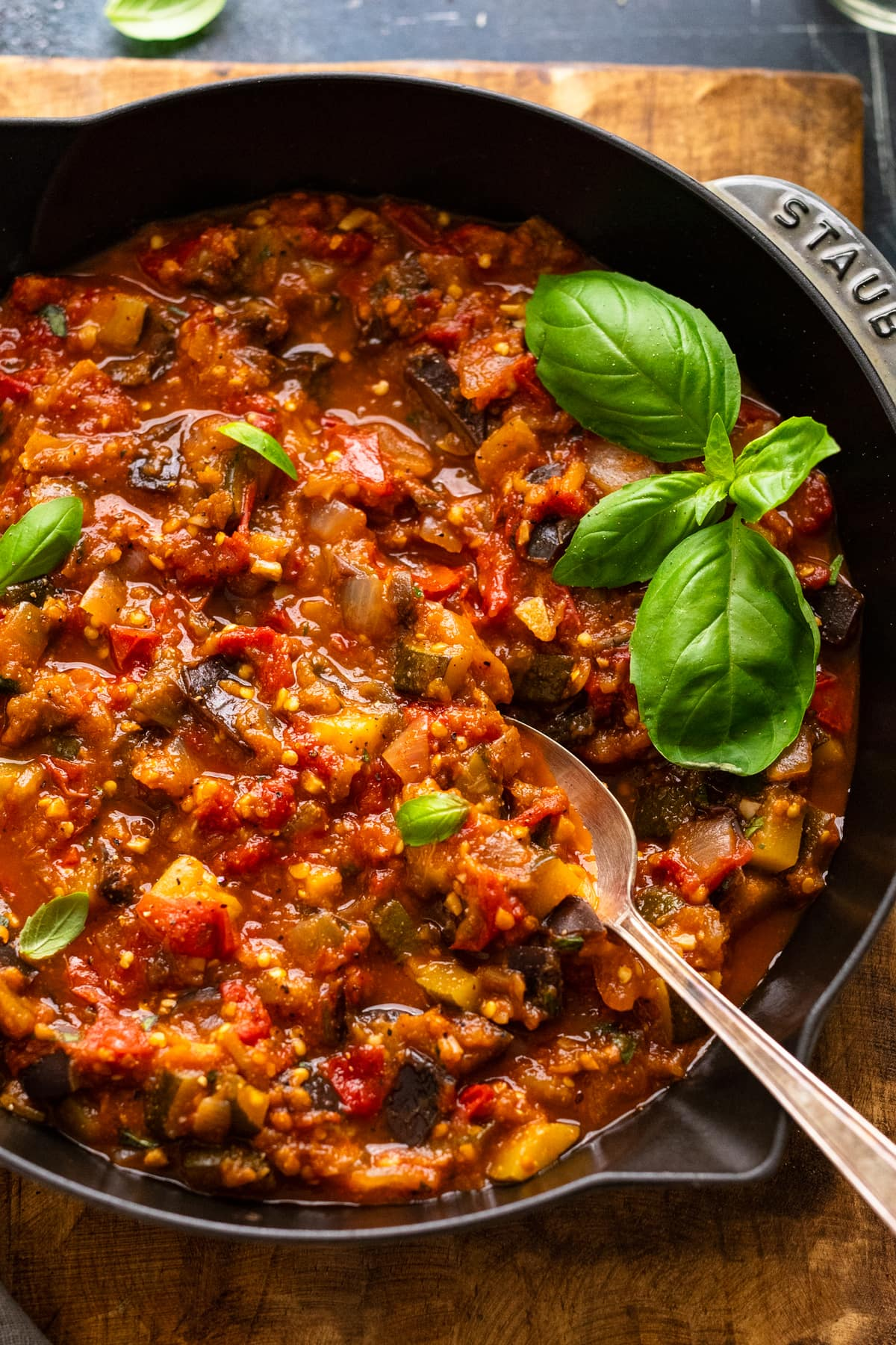 A cast iron pan with eggplant ratatouille in it. The stew is topped with fresh herbs with a spoon in it.