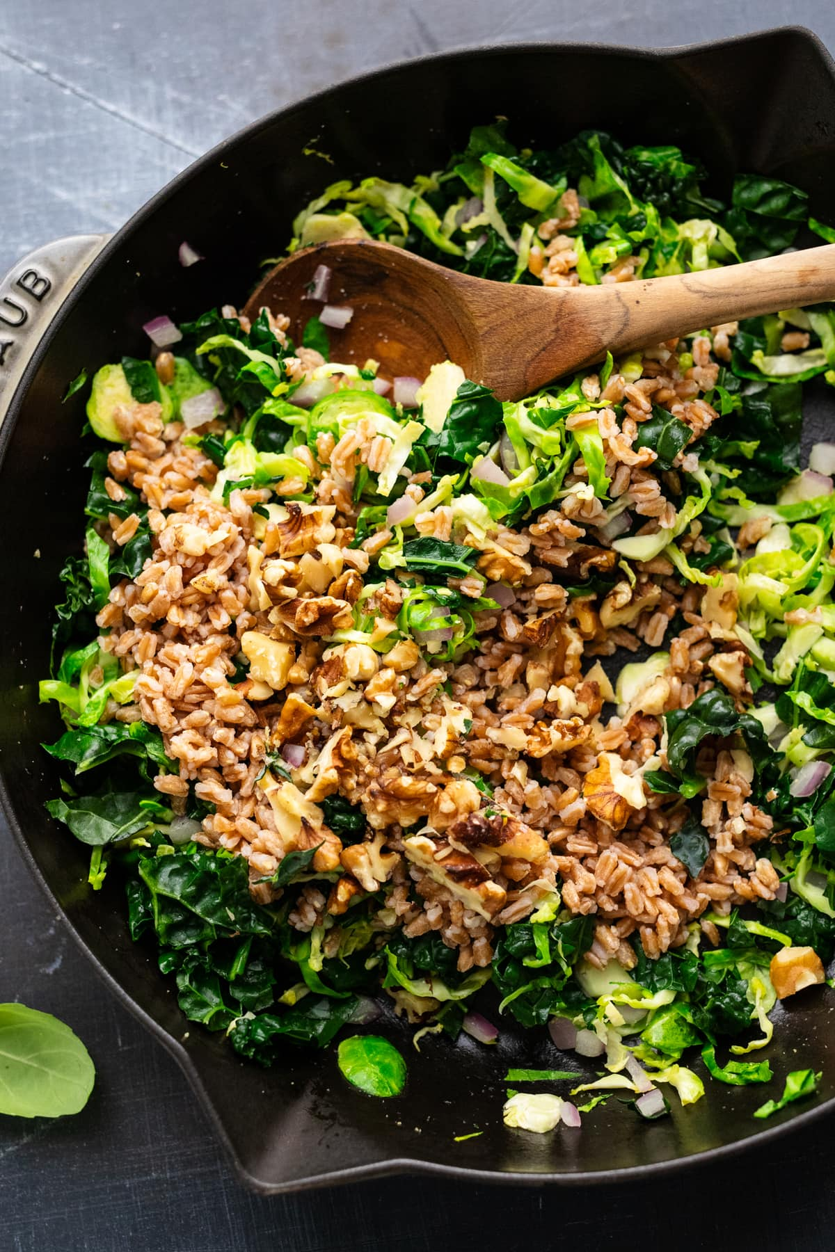 A wooden spoon stirring farro into sautéed greens in a cast iron skillet pan.