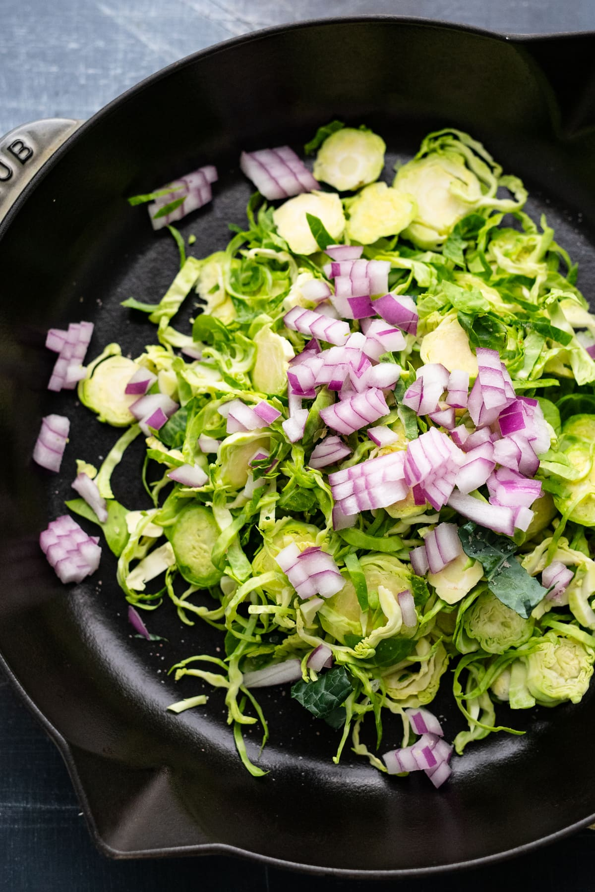 A cast iron pan with shredded brussel sprouts and diced red onion in it.