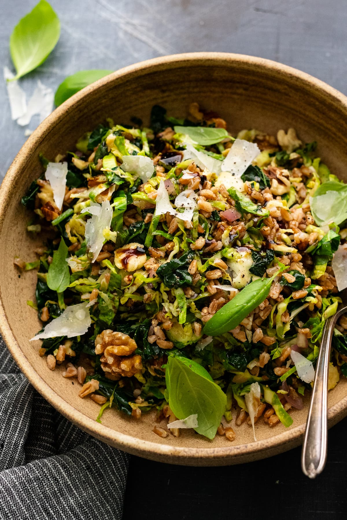 A brown ceramic bowl with kale and brussel sprout salad in it on a gray background, with herbs and nuts arranged around it.
