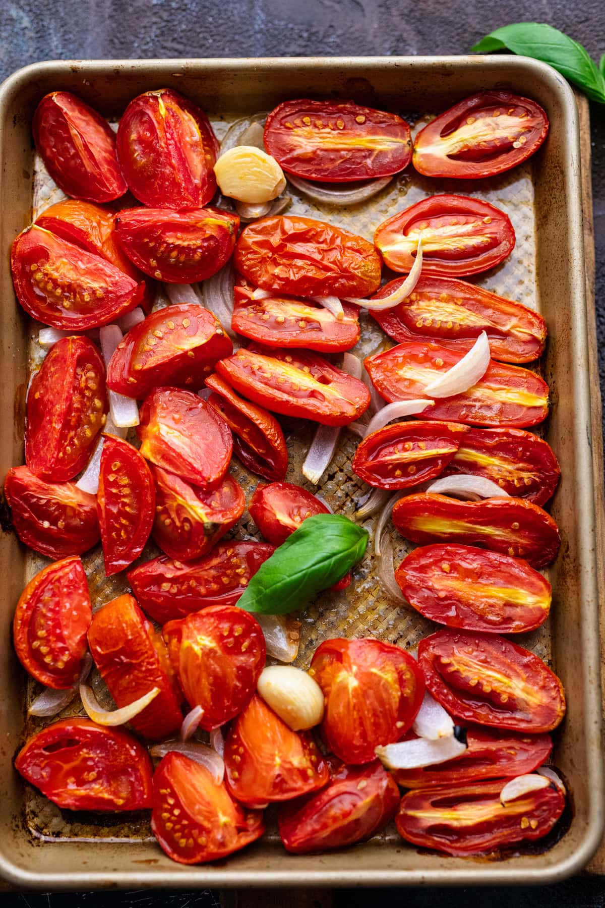 A sheet pan with roasted halved tomatoes and onion slices on it.