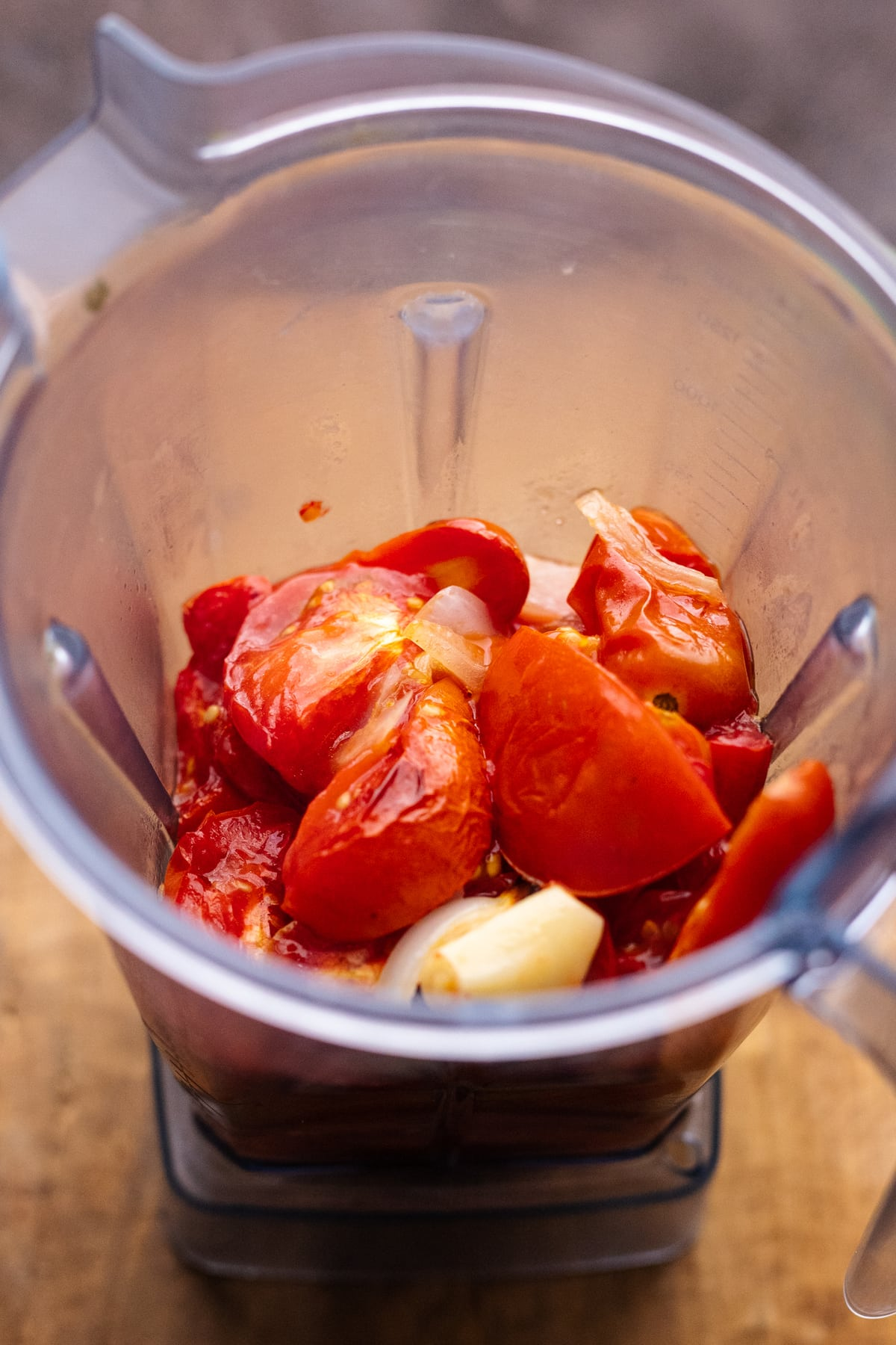 roasted tomatoes and garlic in a plastic blender container on a wooden board.