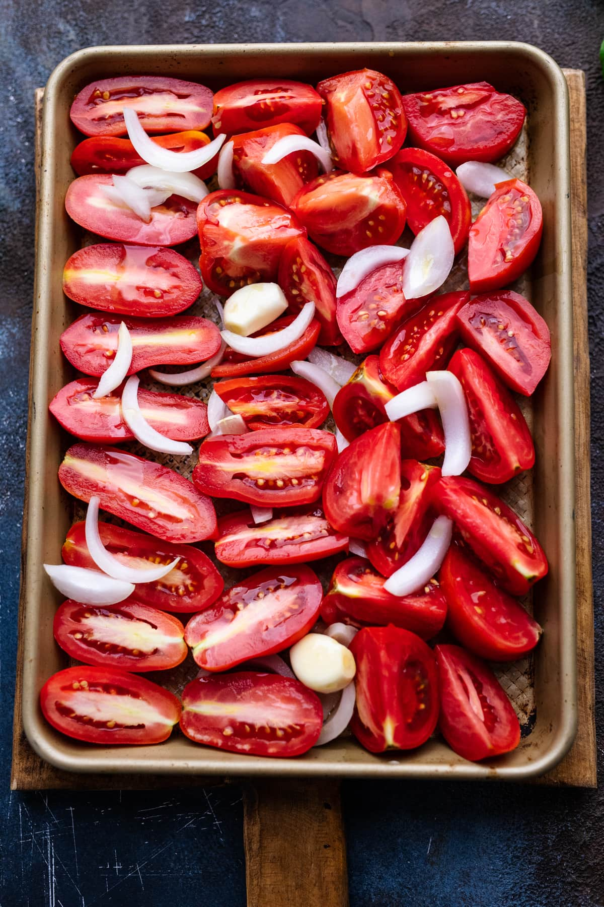 Halved tomatoes and sliced onions on a sheet pan. This pan is arranged on a cutting board that is sitting on a dark gray background.