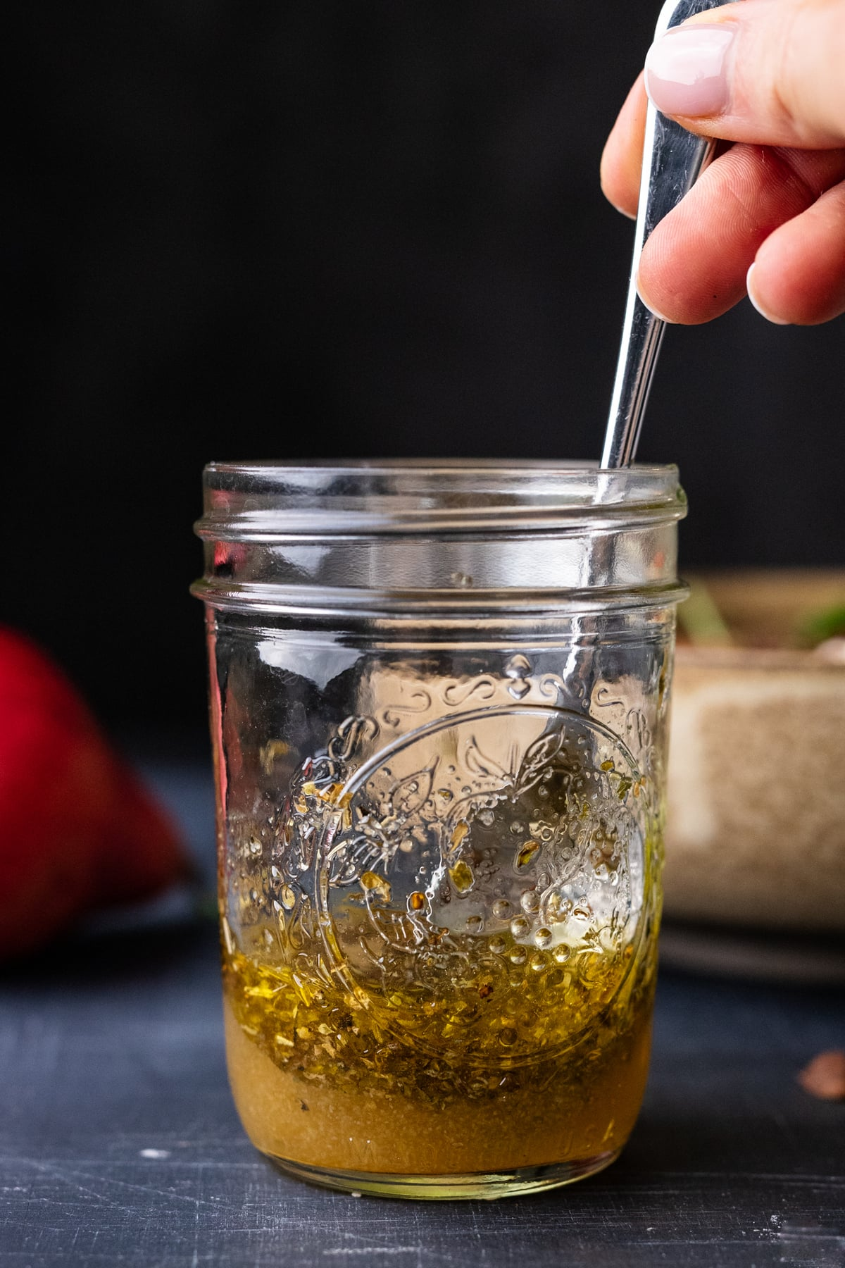 A hand stirring salad dressing in a small jar, with a red pear and bowl sitting behind it.