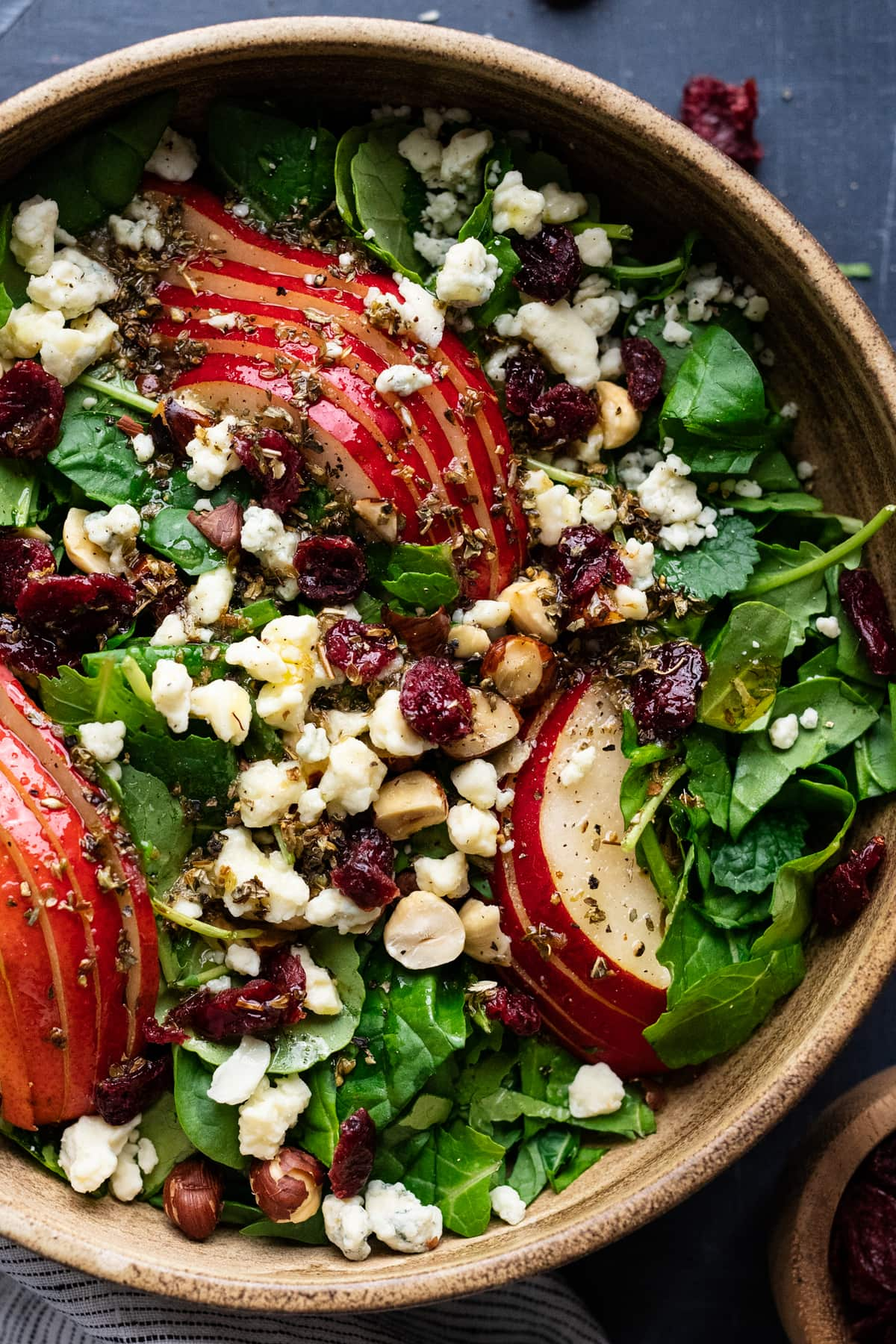 A bowl with pear salad in it on a bed of greens, with crumble cheese on top.